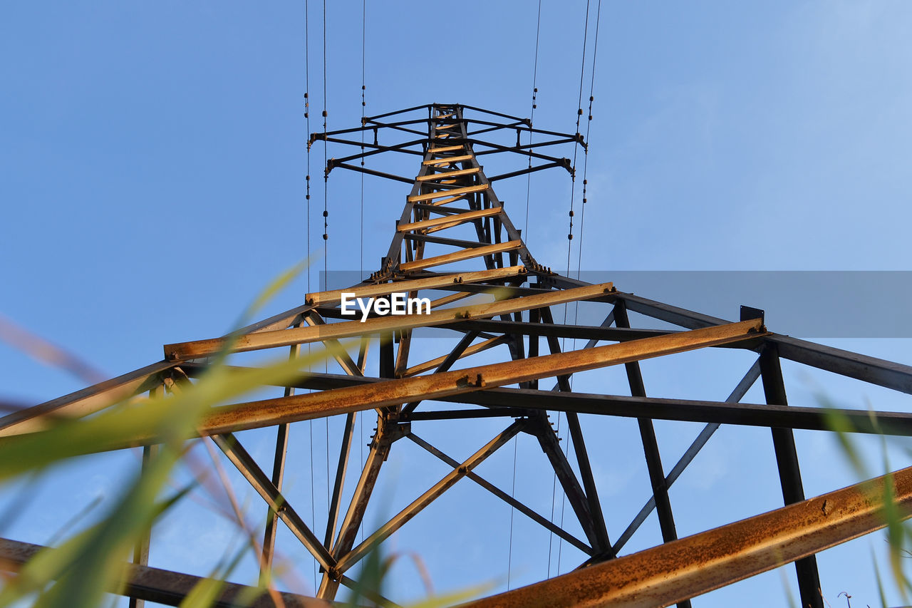 low angle view, sky, connection, built structure, technology, metal, nature, no people, architecture, tower, electricity pylon, electricity, tall - high, day, fuel and power generation, communication, clear sky, cable, blue, outdoors, power supply, global communications, electrical equipment, girder