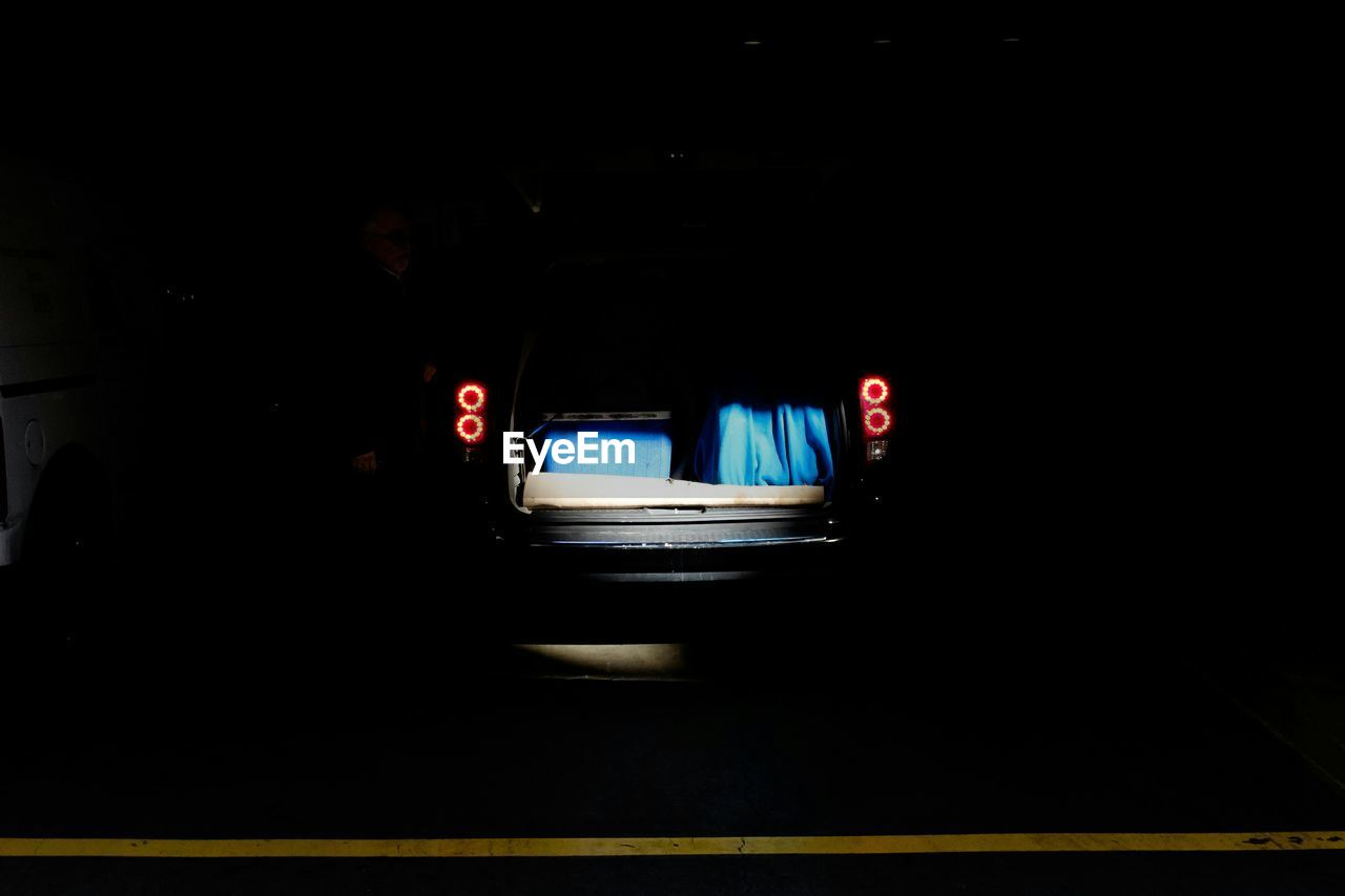 Open car trunk on road during night