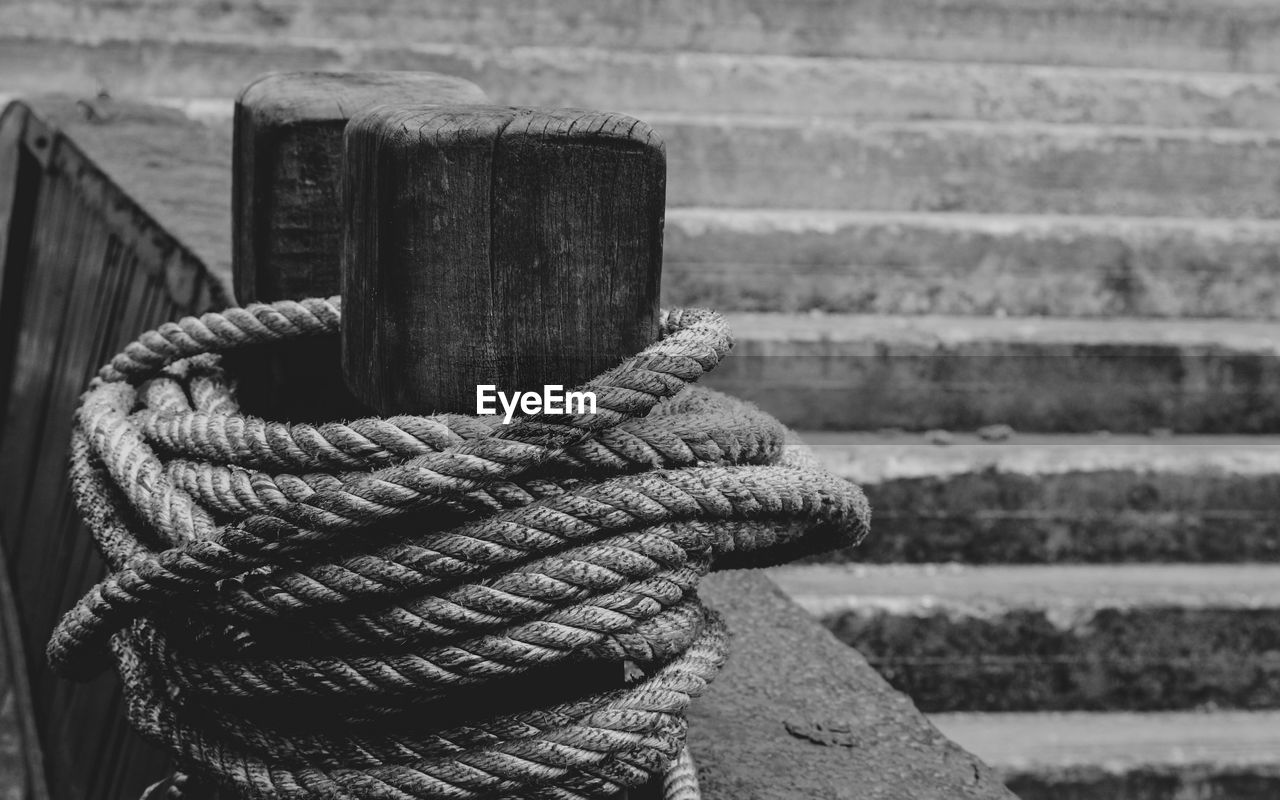 rope, focus on foreground, close-up, no people, day, strength, tied up, post, rolled up, outdoors, pattern, connection, nature, metal, bollard, still life, old, textured, equipment, twisted, wooden post