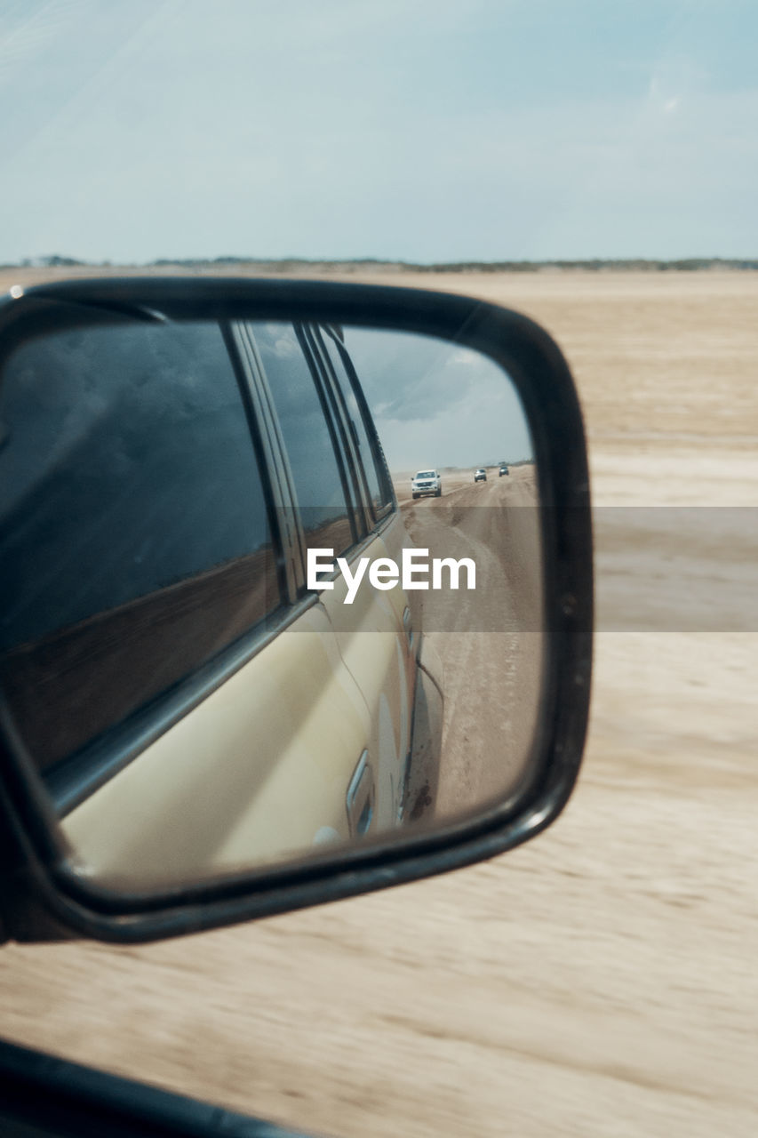 motor vehicle, side-view mirror, car, land vehicle, mode of transportation, reflection, transportation, no people, day, sky, close-up, mirror, nature, outdoors, glass - material, vehicle mirror, focus on foreground, land, window, cloud - sky, road trip