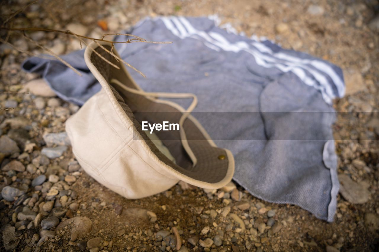 day, no people, clothing, land, nature, close-up, outdoors, focus on foreground, textile, high angle view, white color, shoe, field, abandoned, animal, animal themes, representation, hat, dry, paper, softness