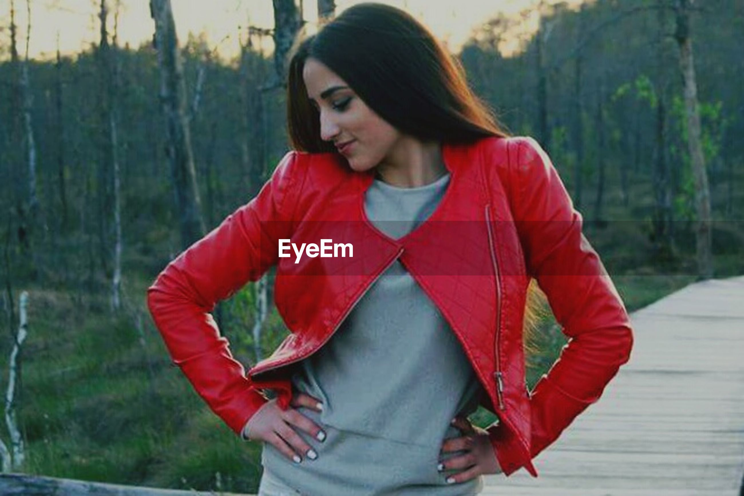 red, lifestyles, leisure activity, young adult, young women, casual clothing, tree, focus on foreground, standing, front view, three quarter length, long hair, person, sitting, looking at camera, waist up