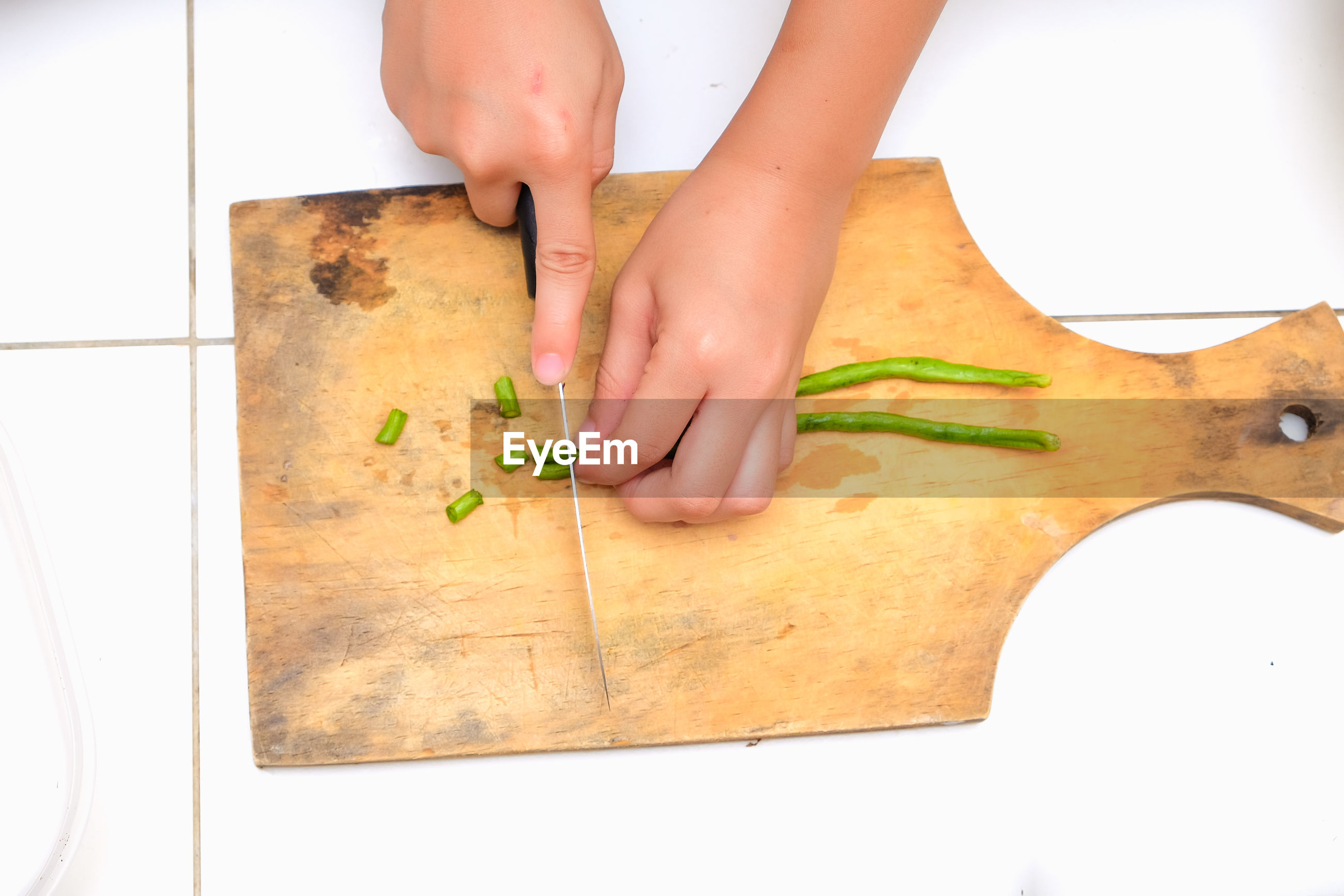 Cropped hands of woman cutting vegetables on board