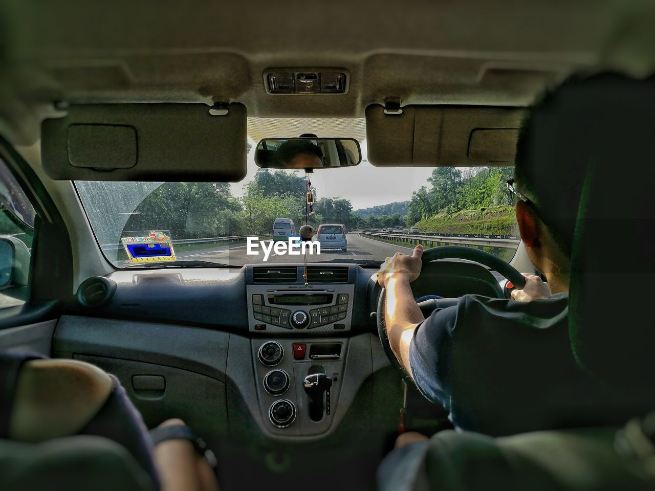 car, vehicle interior, car interior, transportation, mode of transport, land vehicle, real people, steering wheel, dashboard, day, one person, driving, lifestyles, travel, leisure activity, men, vehicle seat, human hand, water, nature, close-up, outdoors, sky