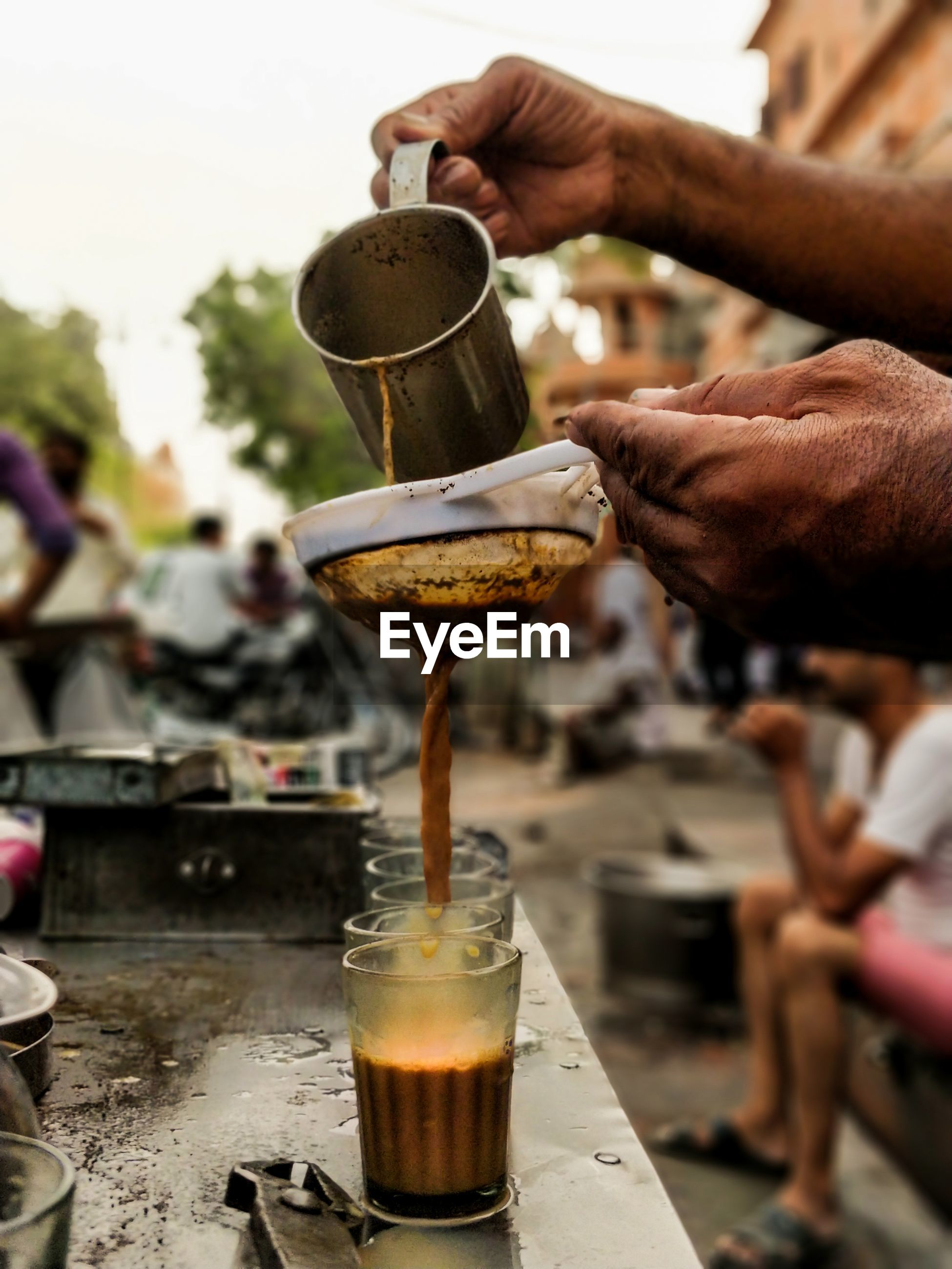 Cropped hands of male vendor preparing tea at market stall