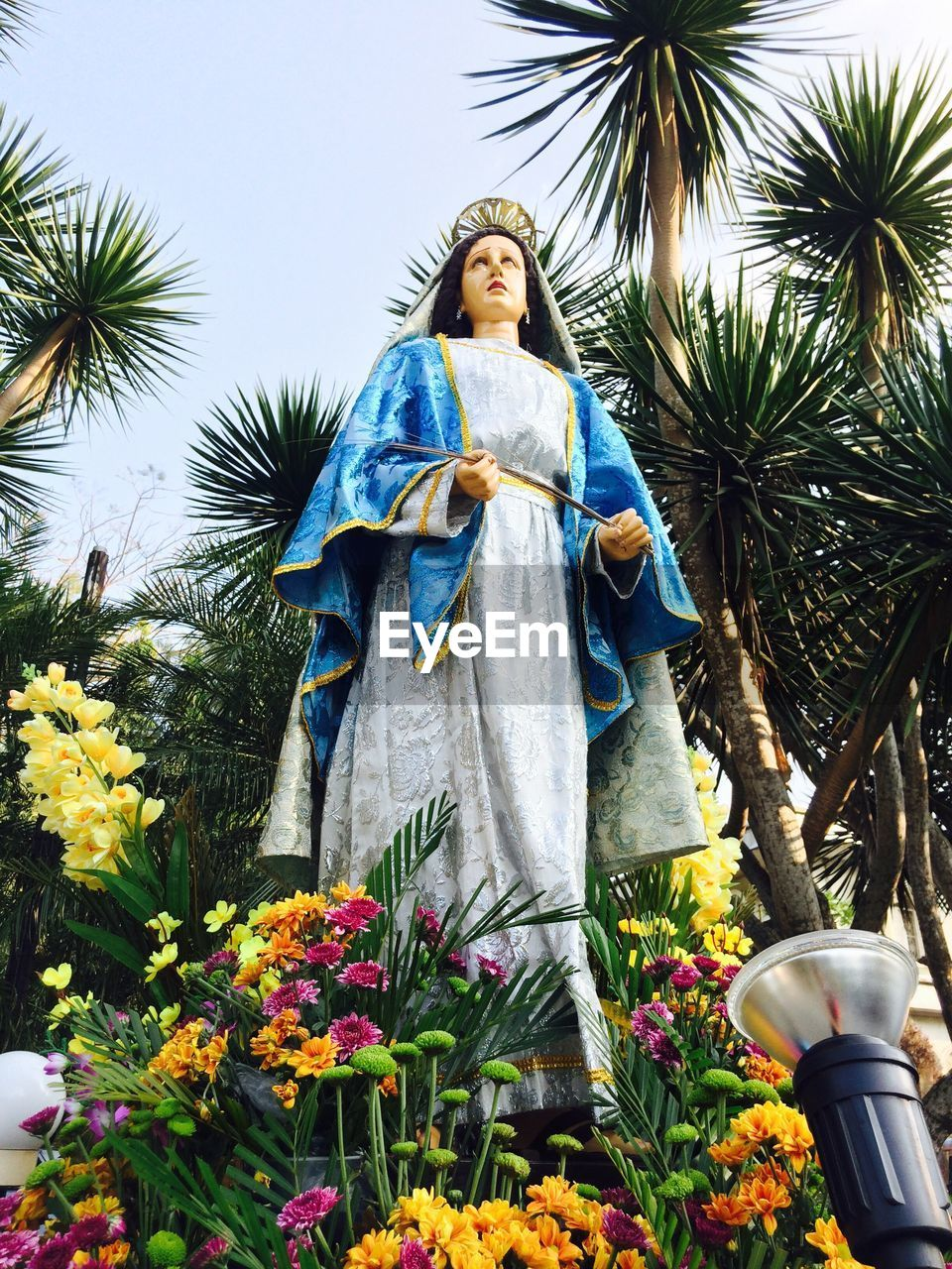 Bouquets around virgin mary statue against trees outside church