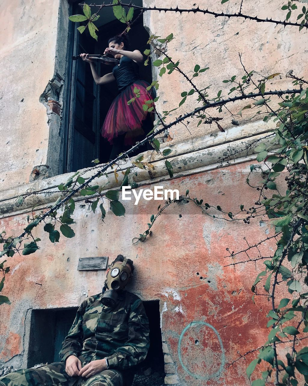 Soldier sitting while woman playing violin at abandoned building