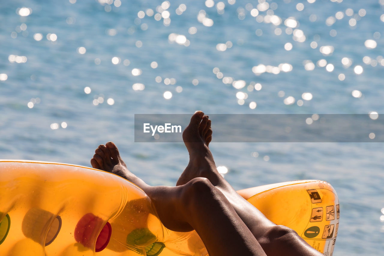 Low Section Of Woman Lying On Inflatable Raft By Sea During Sunny Day