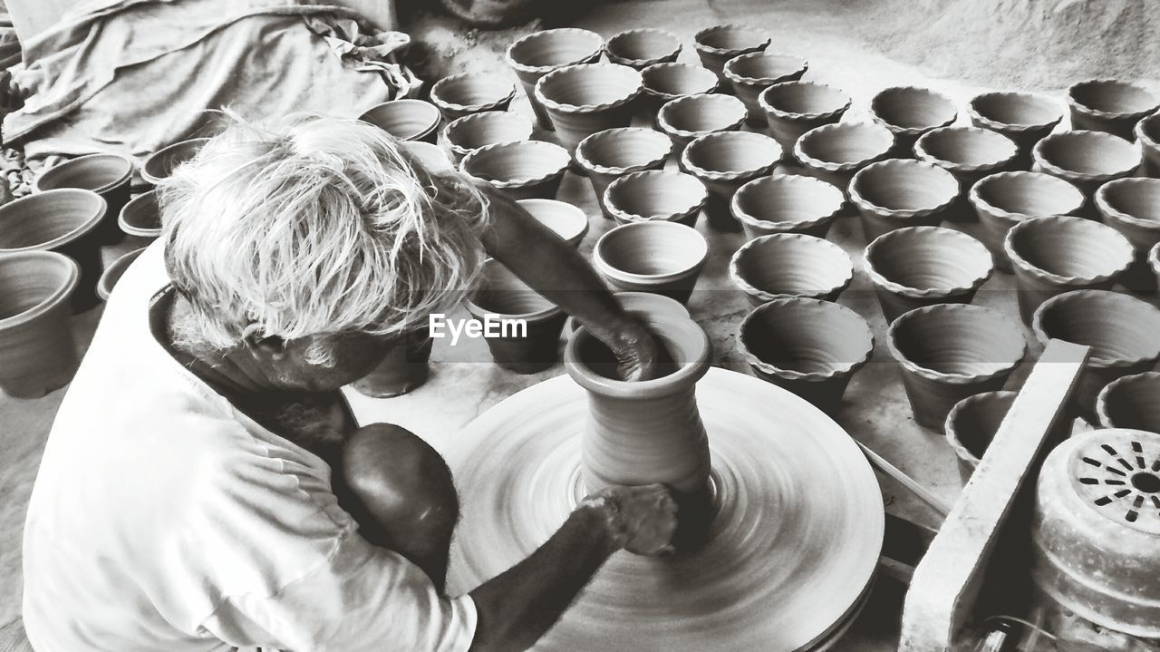 High Angle View Of Potter Making Pots At Workshop