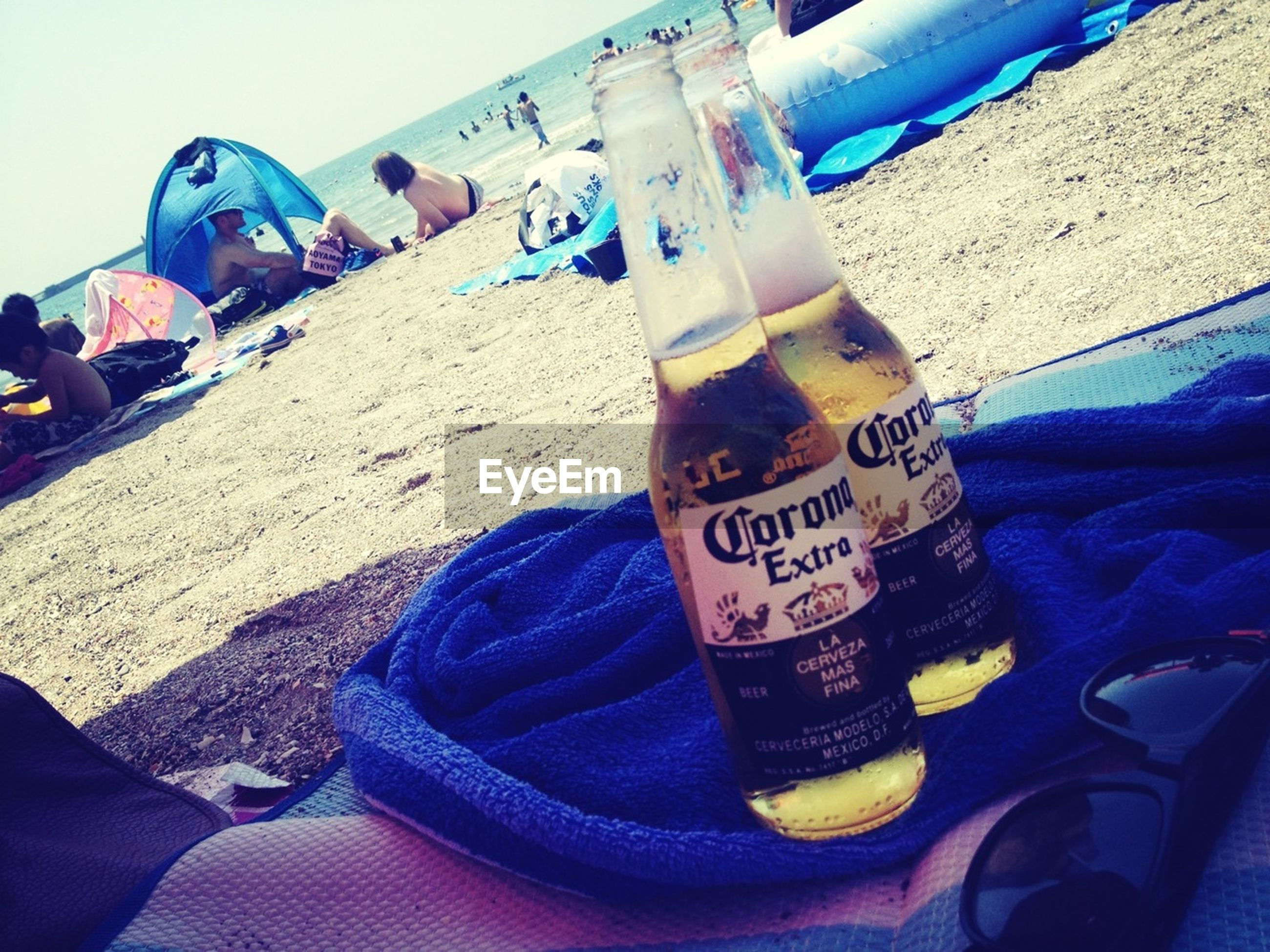text, western script, blue, communication, sunlight, lifestyles, men, day, leisure activity, outdoors, transportation, incidental people, mode of transport, sky, close-up, sea, beach, low section