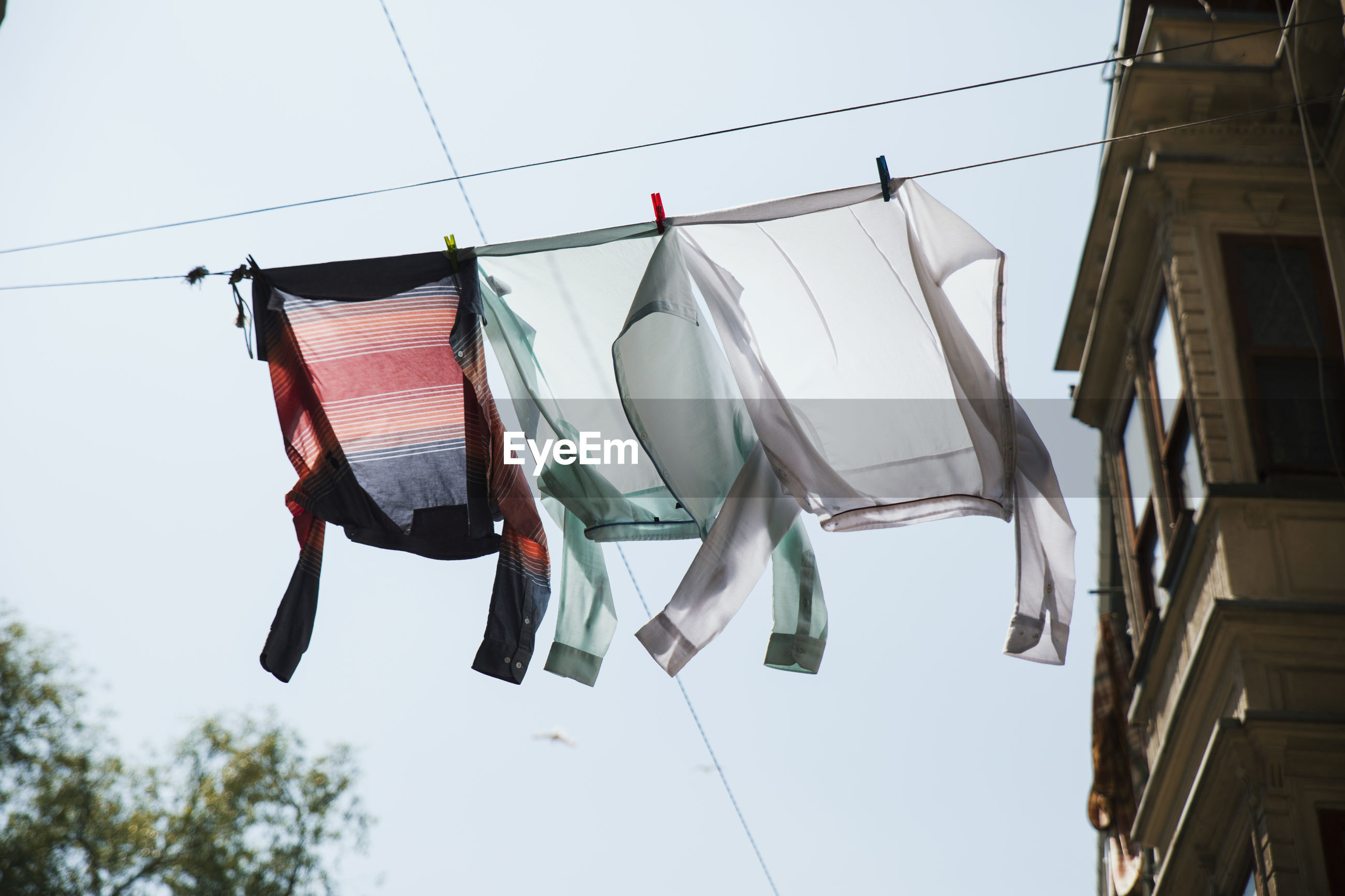 Low angle view of clothes drying on clothesline by building against sky