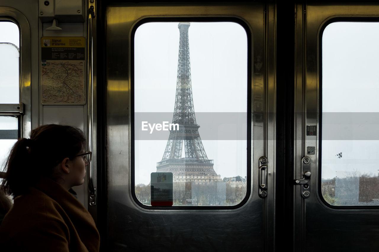Woman looking at eiffel tower through train window