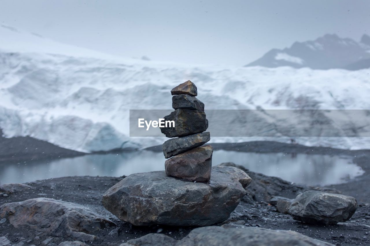 Stack of rocks against lake during winter