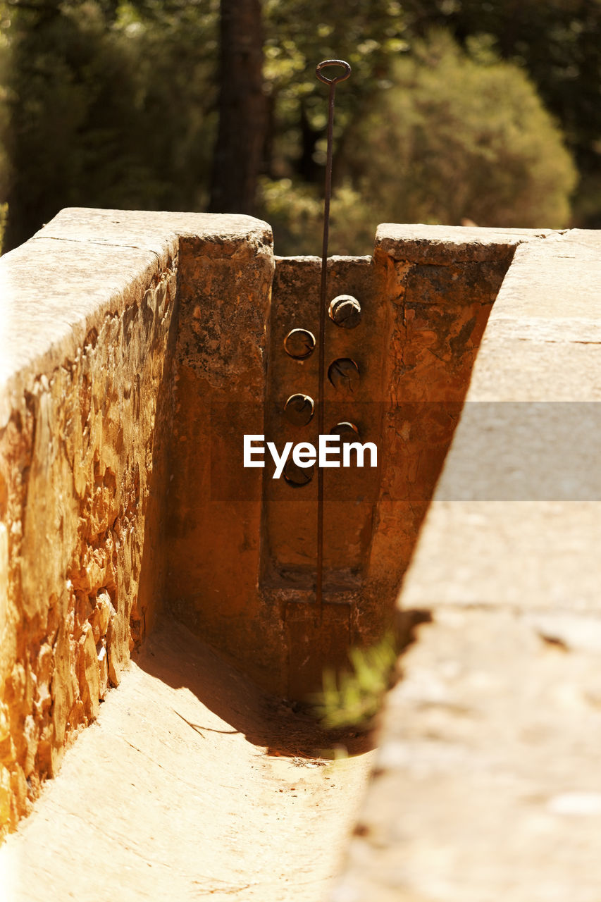 sunlight, day, focus on foreground, no people, close-up, metal, nature, wood - material, outdoors, rusty, selective focus, sunny, shadow, wall - building feature, architecture, brown, wall, built structure, plant, tree