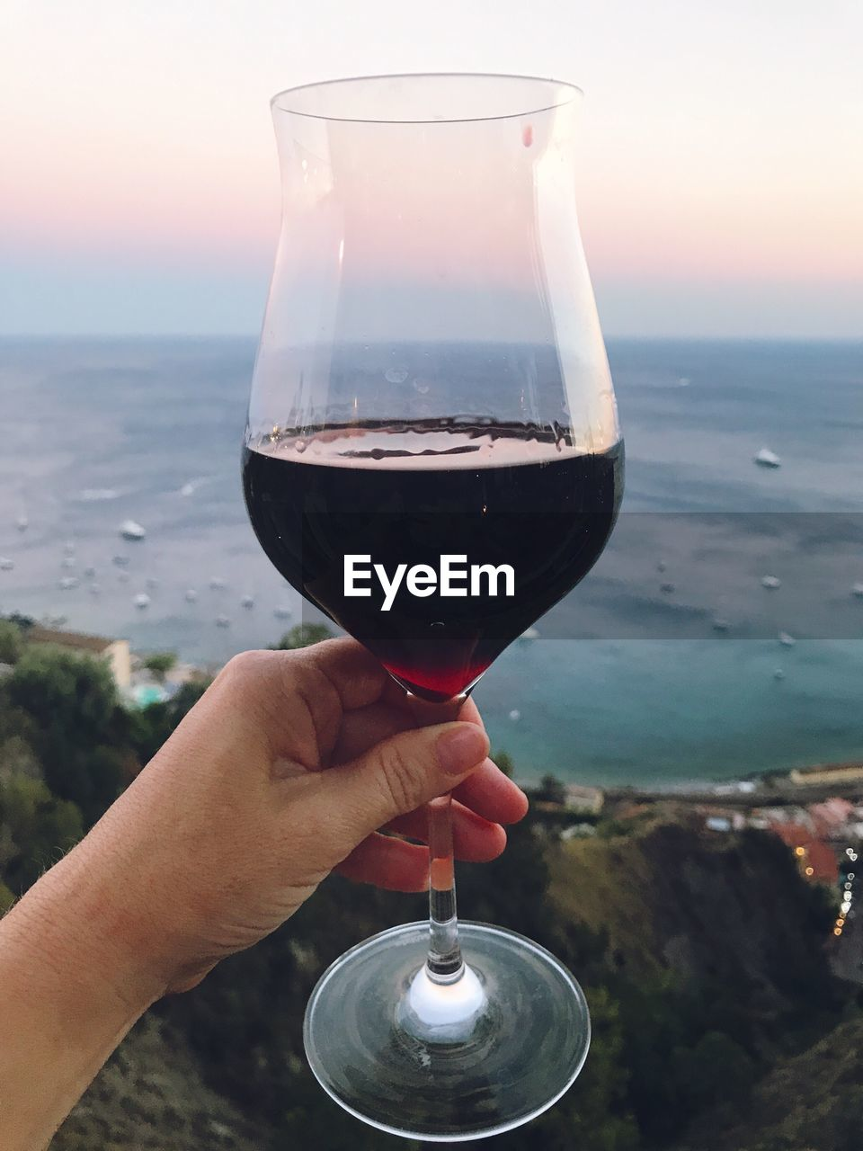 human hand, wineglass, holding, real people, drink, wine, human body part, food and drink, focus on foreground, one person, outdoors, alcohol, refreshment, water, close-up, sunset, lifestyles, men, drinking glass, sea, sky, day, nature, women, beauty in nature, food, freshness, people
