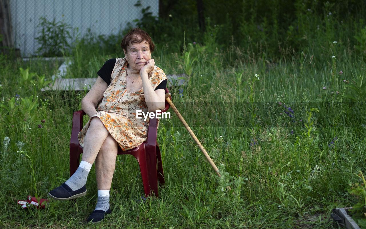 Full Length Of Senior Woman Sitting On Chair In Back Yard