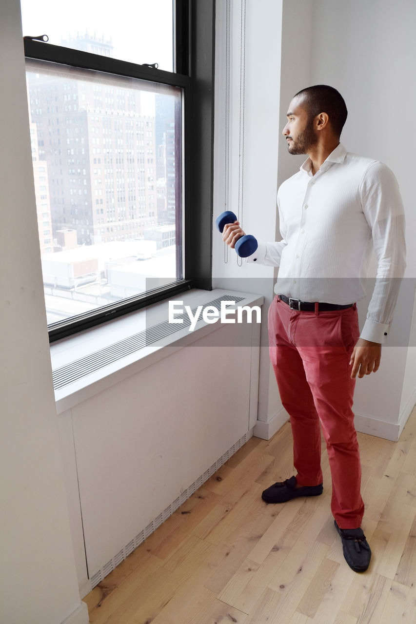 Man Lifting Dumbbell While Looking Through Window