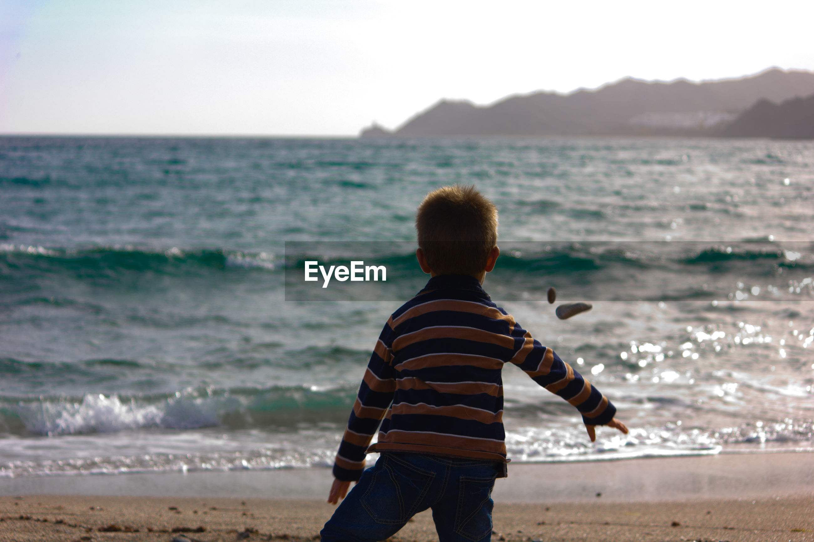 Rear view of boy standing at beach