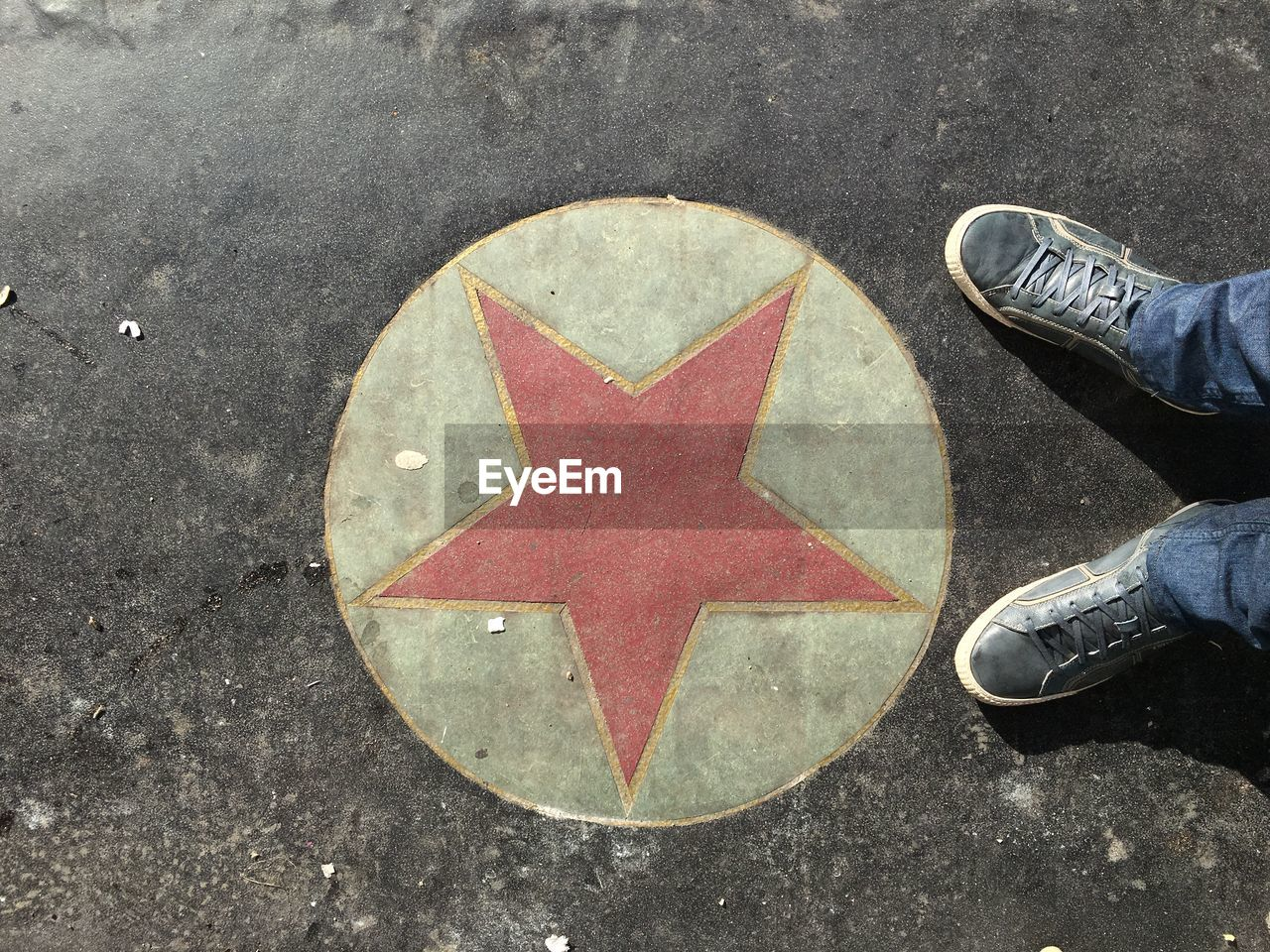 Low Section Of Person Standing By Star Shaped Sign On Road