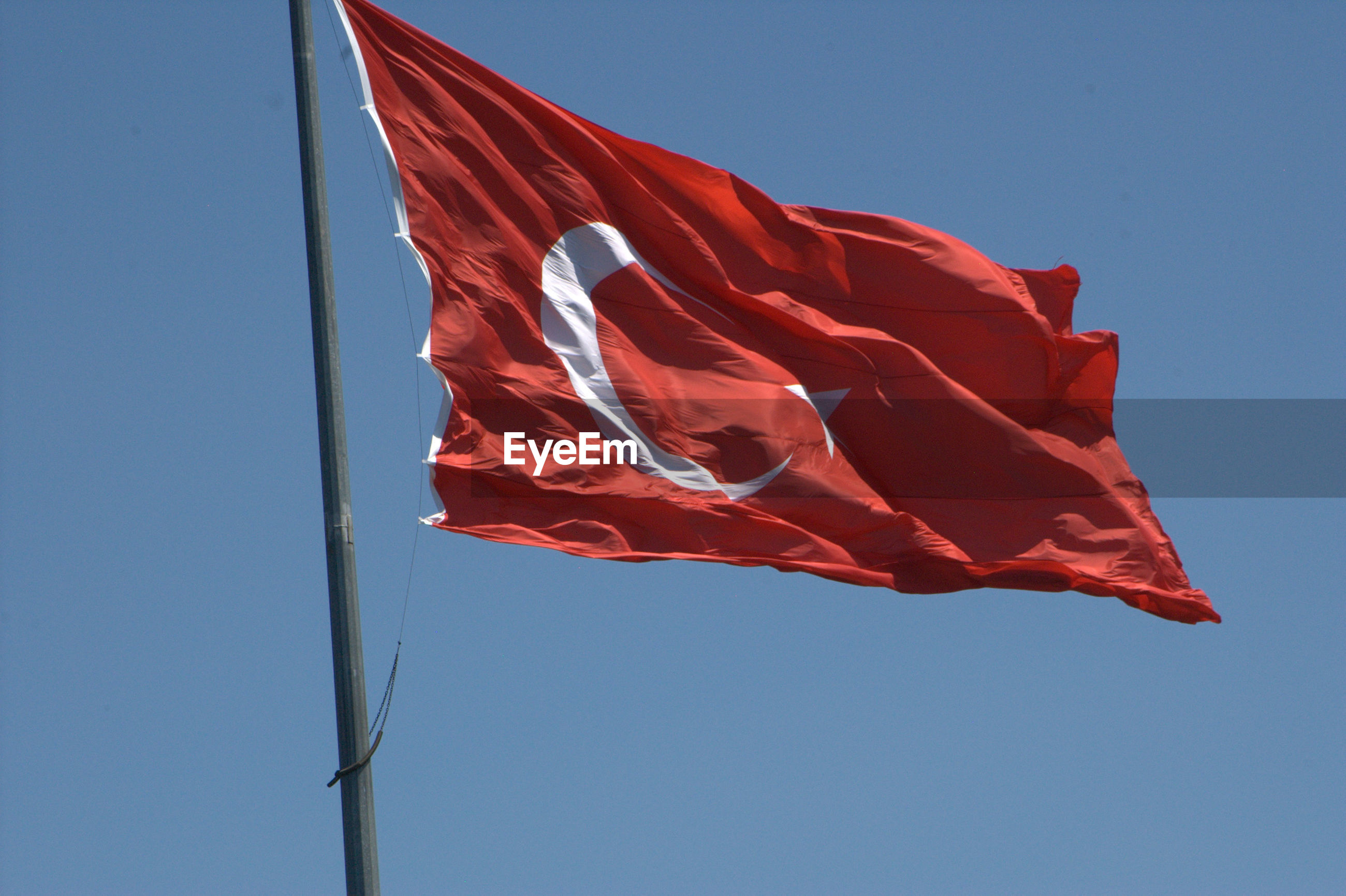 Low angle view of turkish flag against clear blue sky