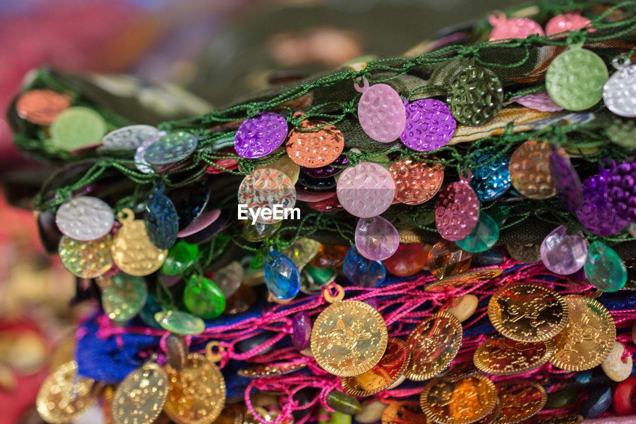 multi colored, close-up, no people, art and craft, decoration, focus on foreground, indoors, choice, large group of objects, variation, abundance, craft, shiny, selective focus, still life, creativity, pattern, high angle view, for sale, red, retail display, luxury