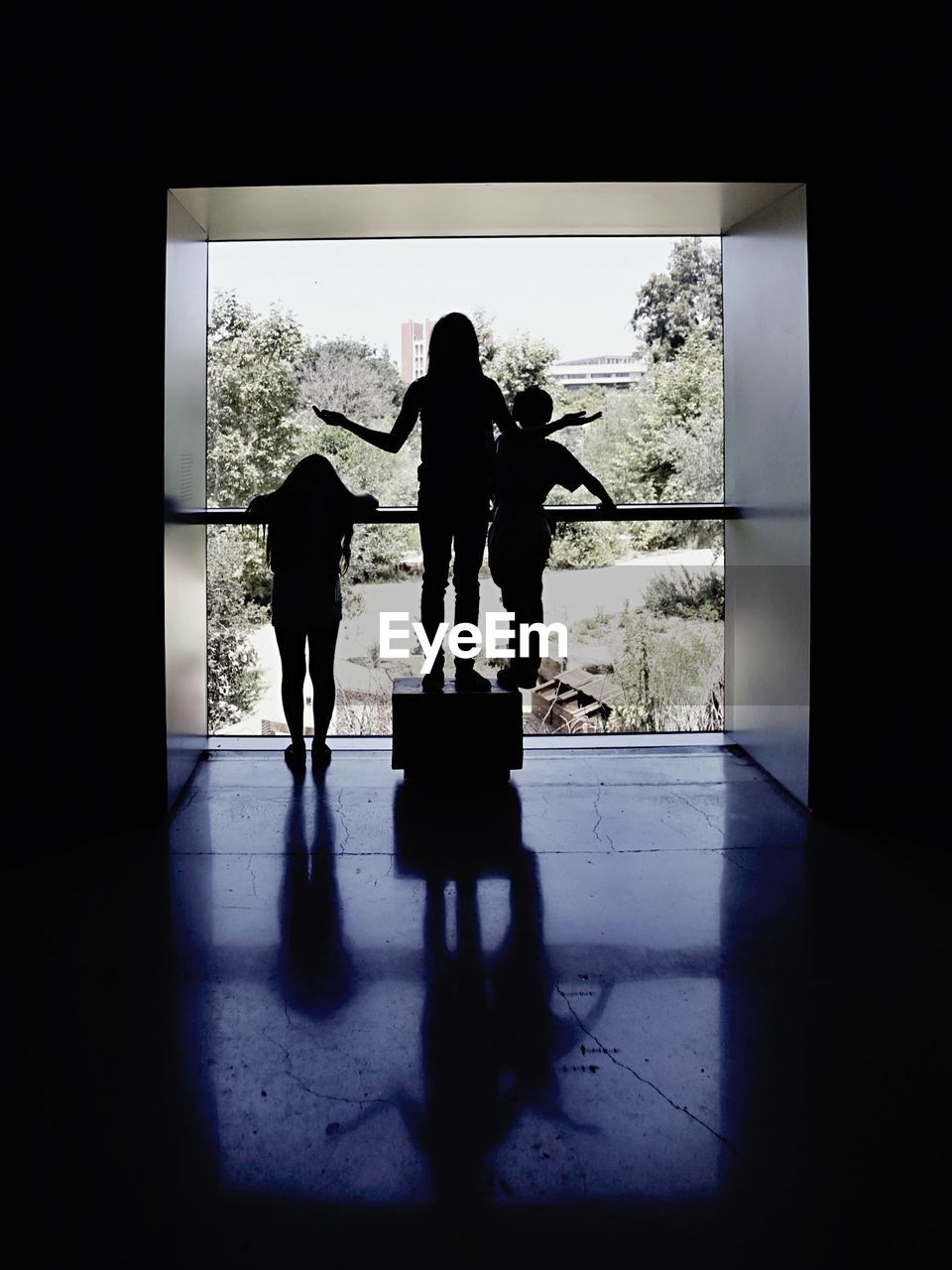 Silhouette of three people leaning against railing
