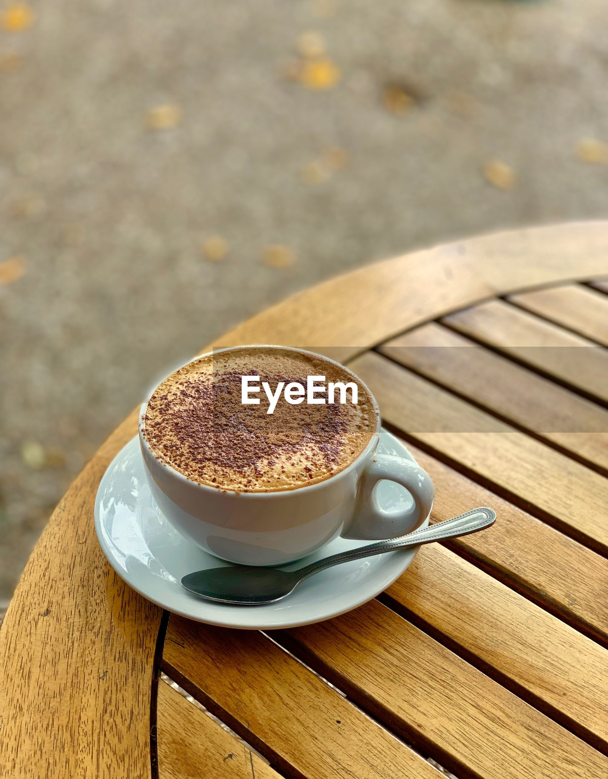 HIGH ANGLE VIEW OF COFFEE CUP ON TABLE AGAINST WOODEN BACKGROUND