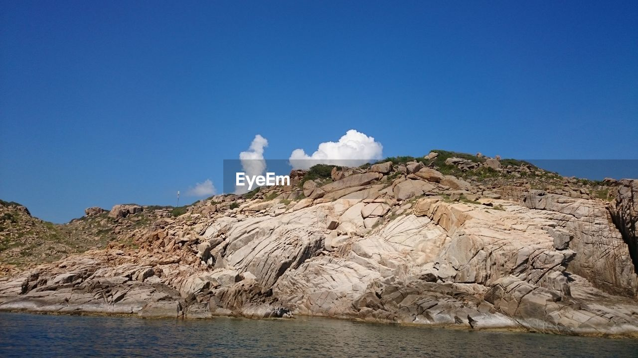 Sea And Rock Formations Against Blue Sky