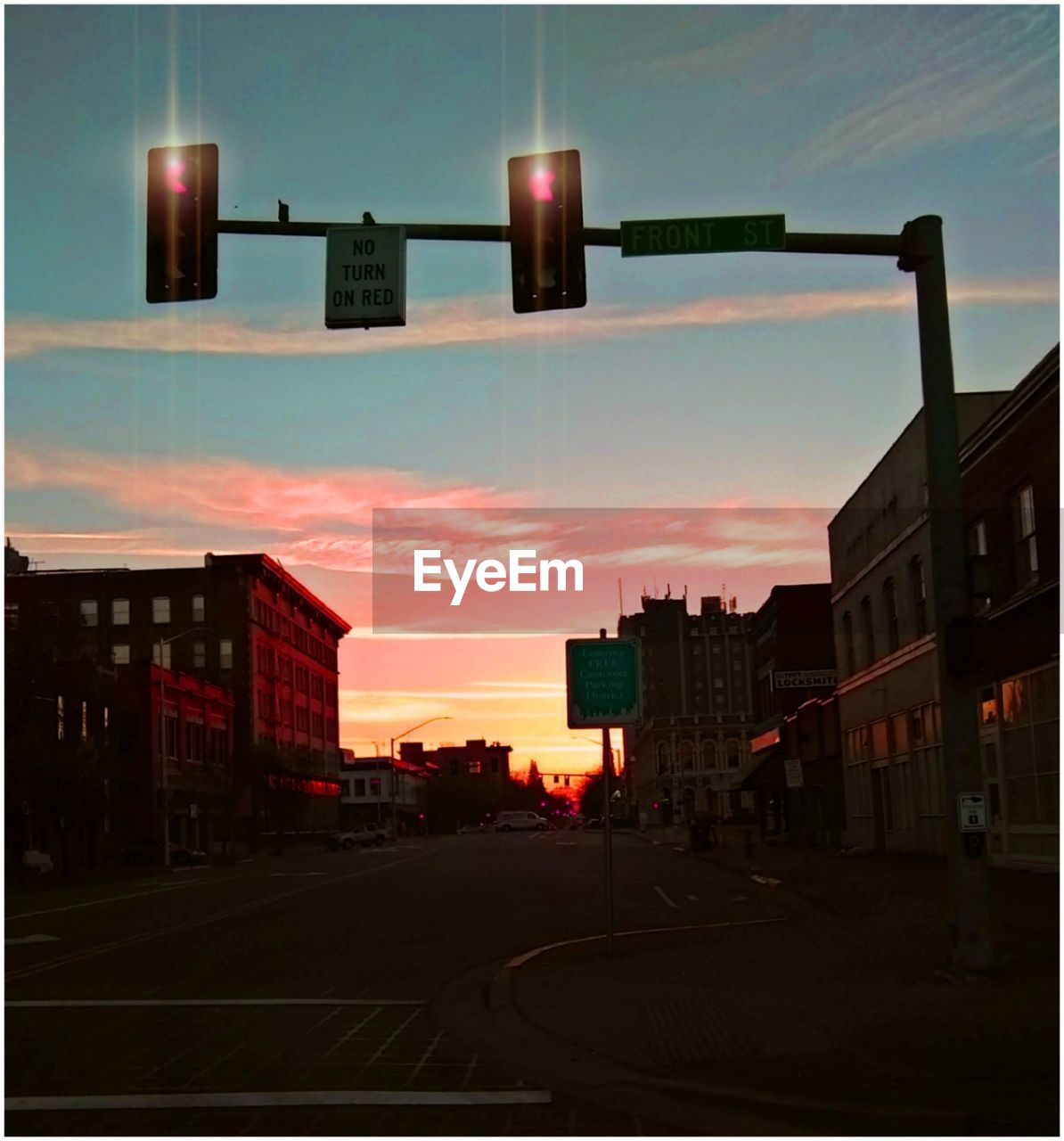 architecture, city, sign, building exterior, sky, built structure, sunset, street, cloud - sky, stoplight, road, transportation, no people, light, dusk, road signal, nature, guidance, direction, illuminated, outdoors