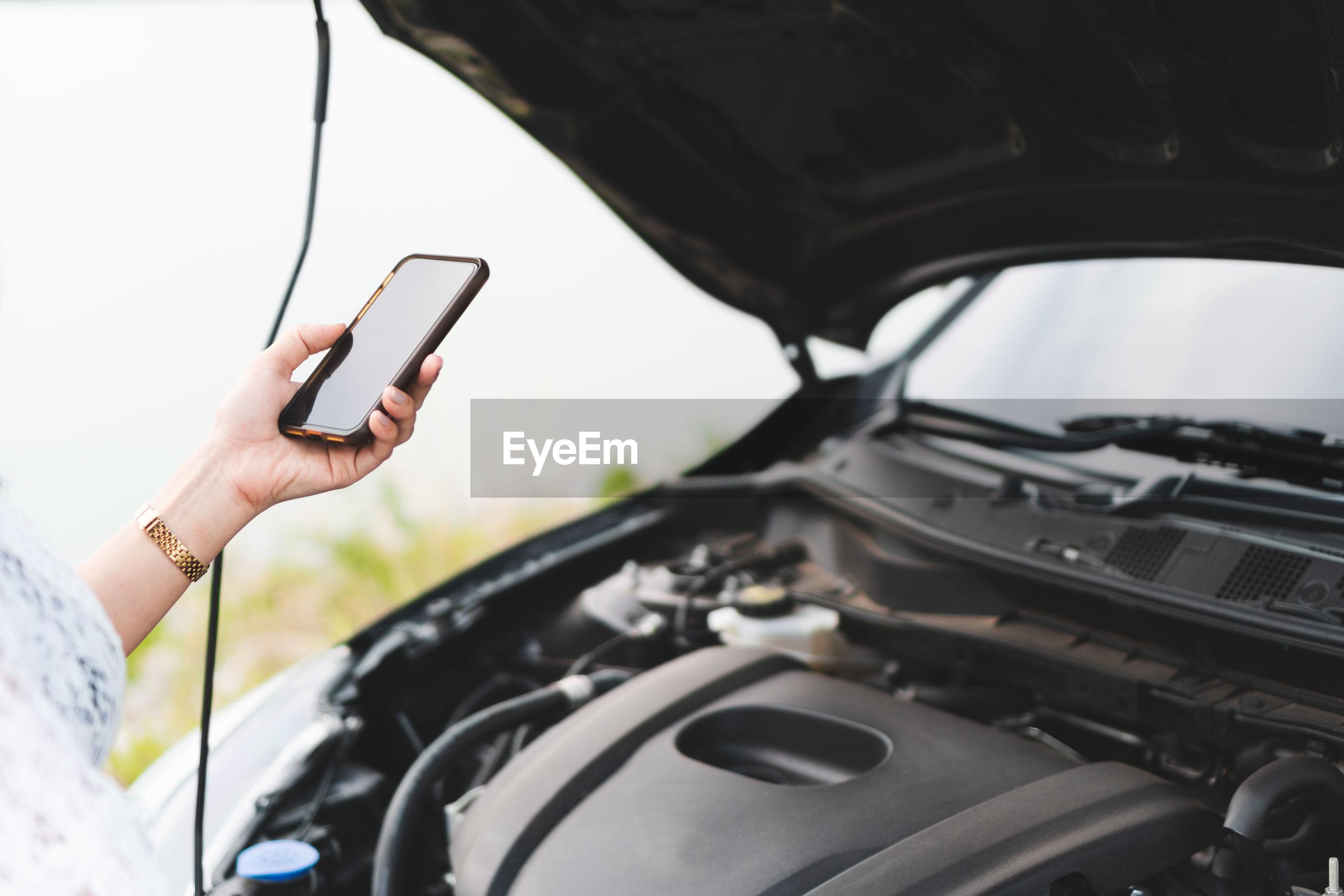 Woman using mobile phone while repairing car outdoors