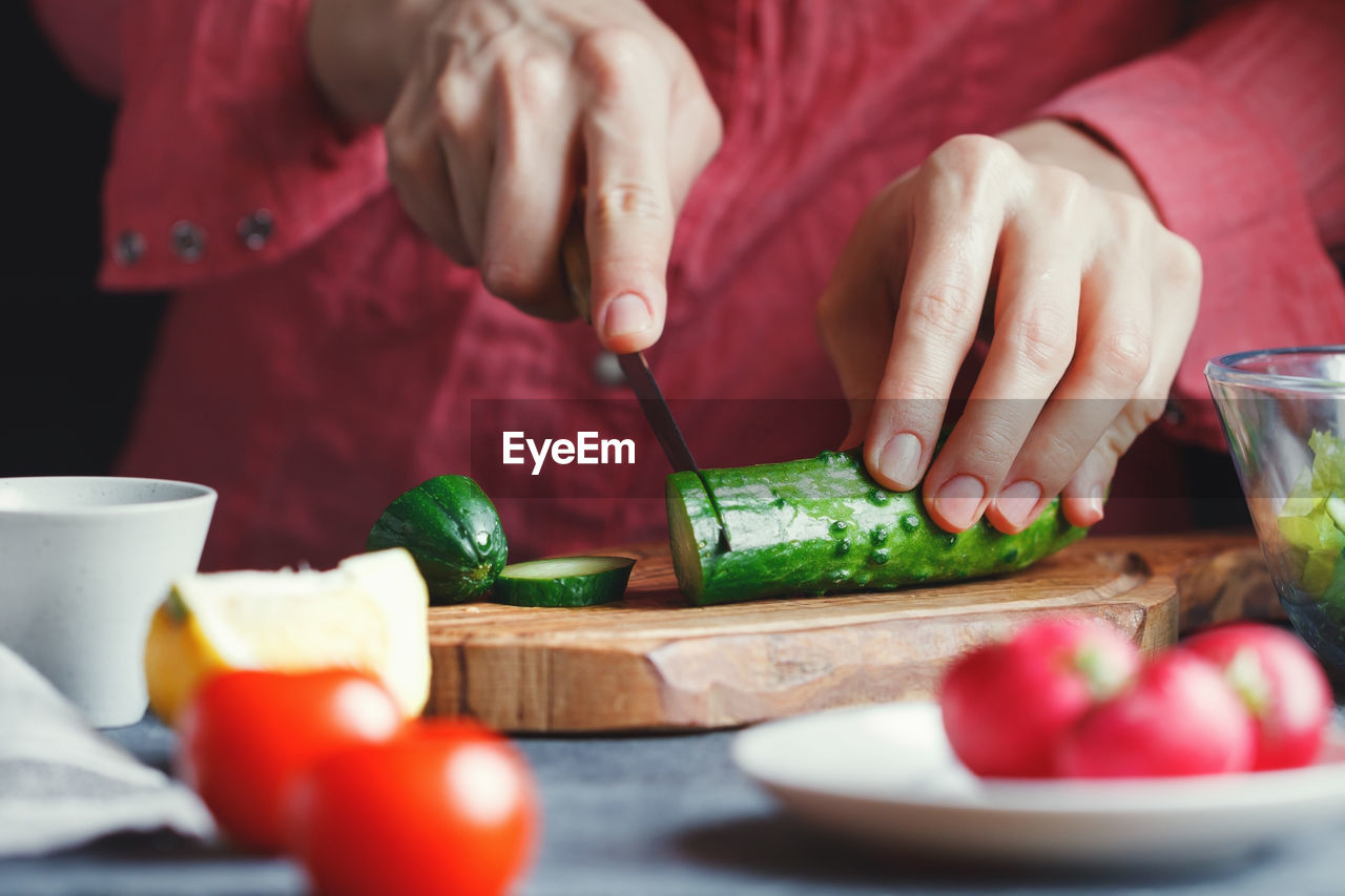 preparation, food and drink, vegetable, real people, kitchen knife, chopping, healthy eating, cutting, freshness, human hand, holding, one person, table, food, indoors, cutting board, midsection, preparing food, lifestyles, bowl, men, close-up, day