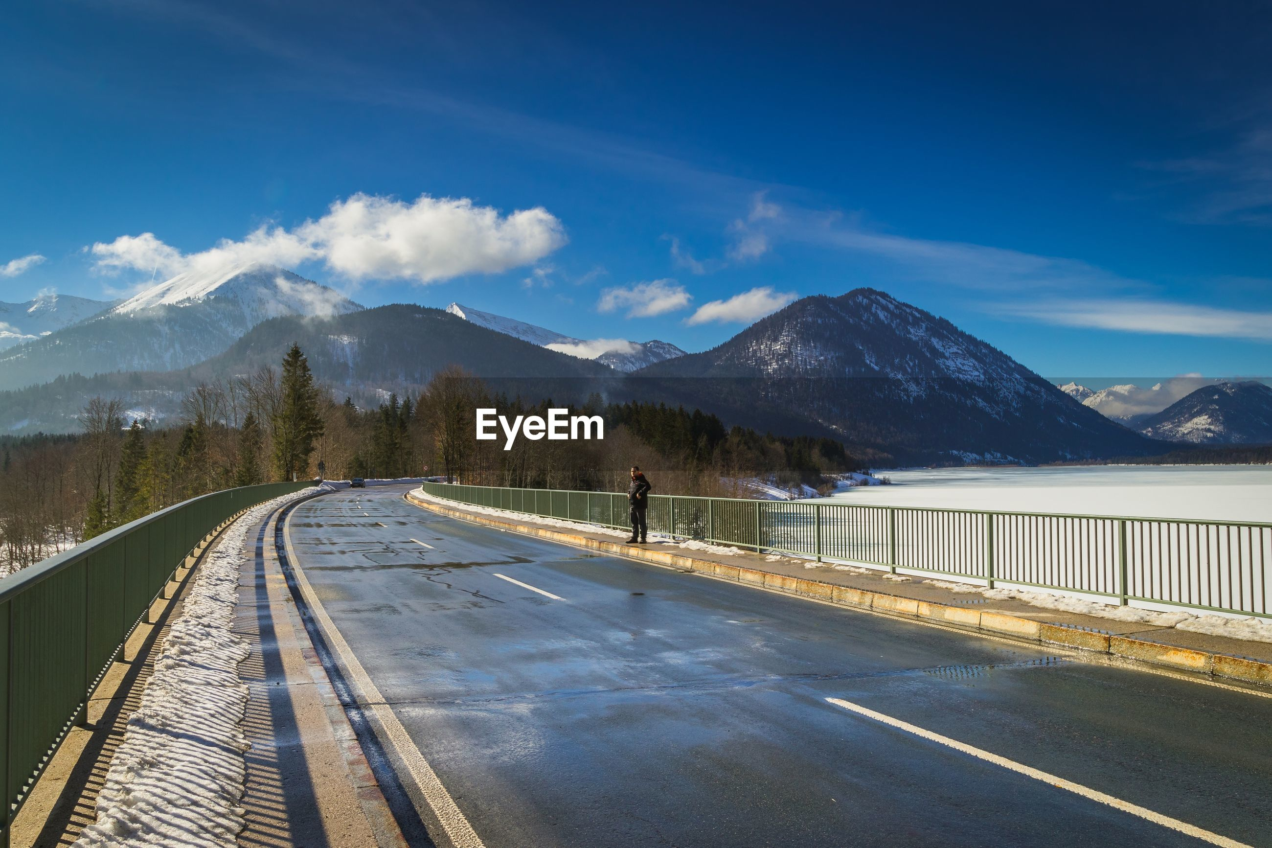Full length of man standing on road leading towards mountains against sky
