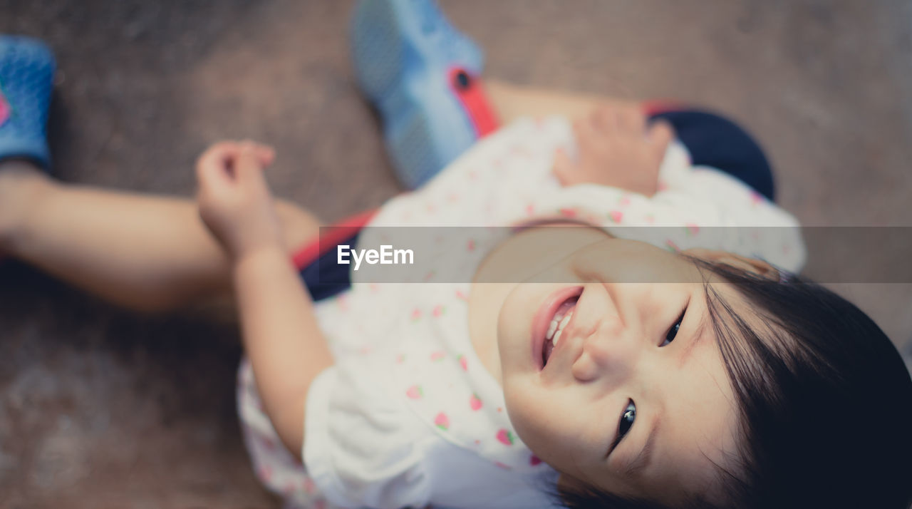 High angle portrait of cheerful baby girl sitting on floor