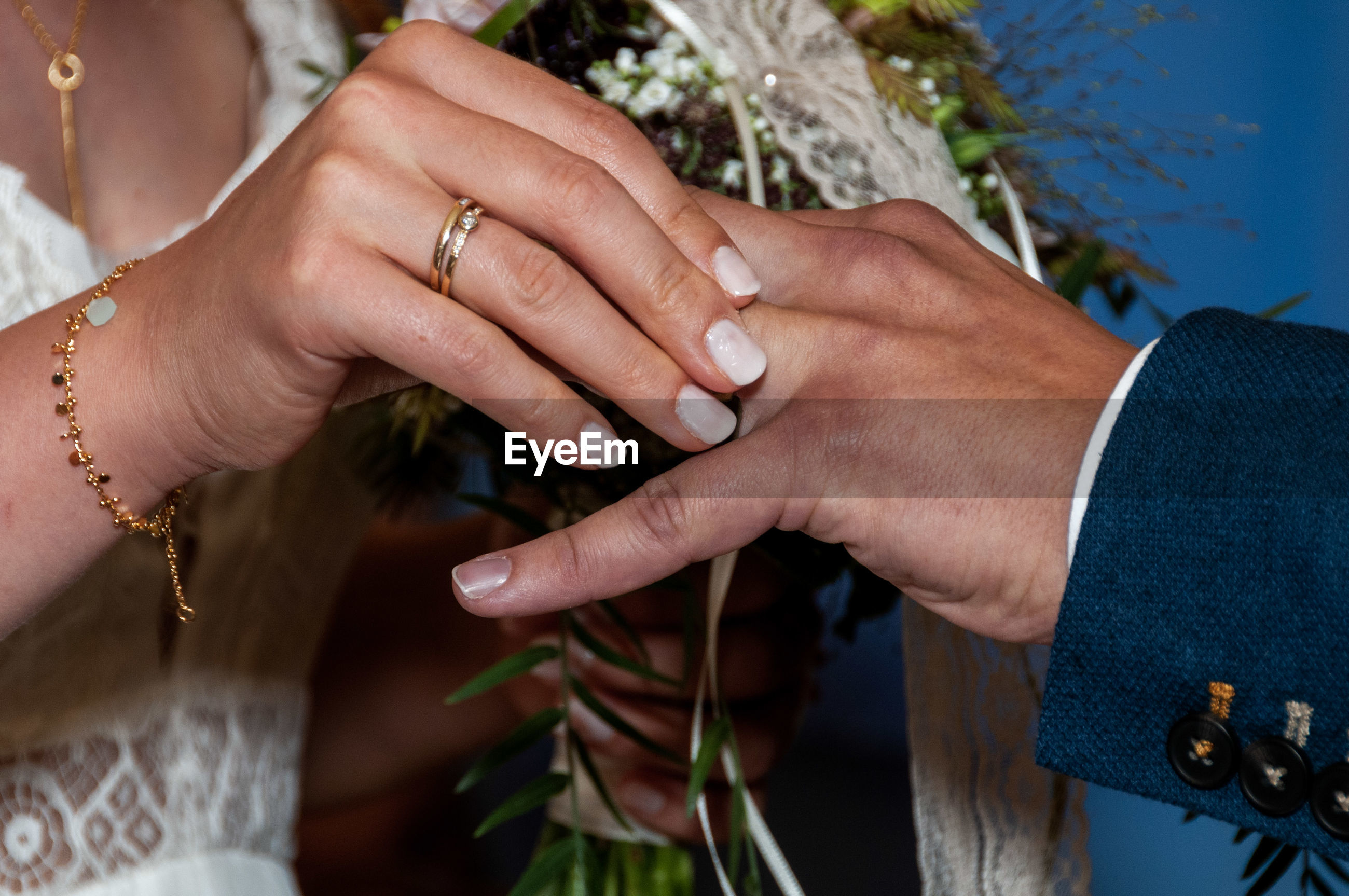 Midsection of bride holding groom finger