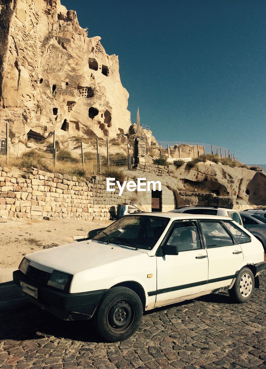 car, transportation, land vehicle, mode of transport, history, day, architecture, clear sky, rock - object, outdoors, built structure, sunlight, ancient, travel destinations, old ruin, no people, arid climate, ancient civilization, building exterior, mountain, nature, sky