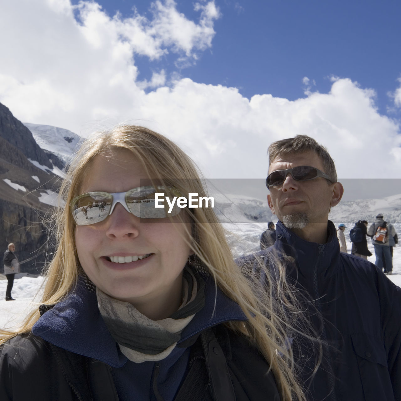 Close-Up Of Happy Teenage Girl With Father At Athabasca Glacier In Jasper National Park Against Sky