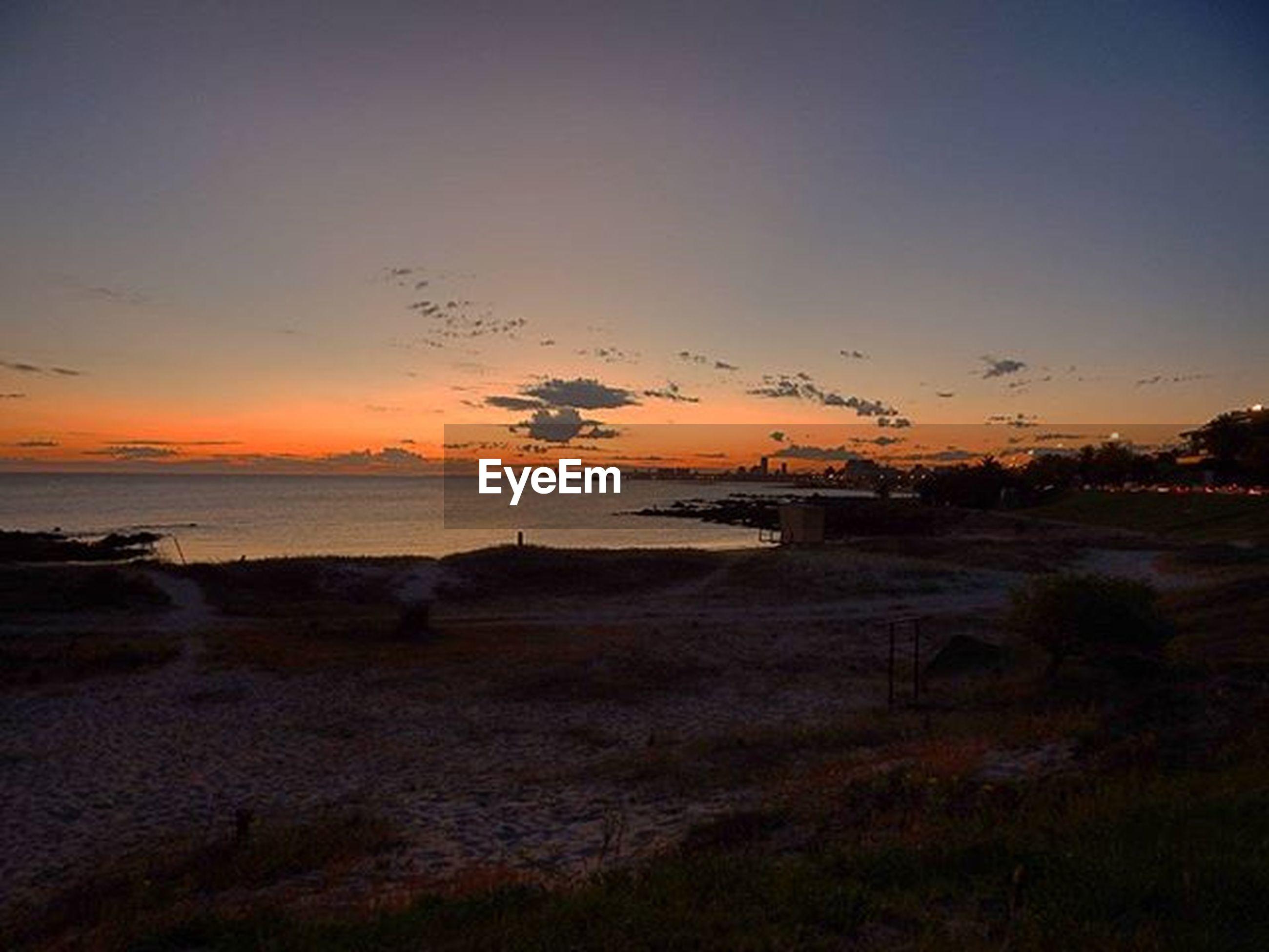 sunset, tranquil scene, scenics, tranquility, sea, water, beauty in nature, beach, sky, orange color, horizon over water, silhouette, nature, idyllic, shore, landscape, non-urban scene, dusk, sand, remote