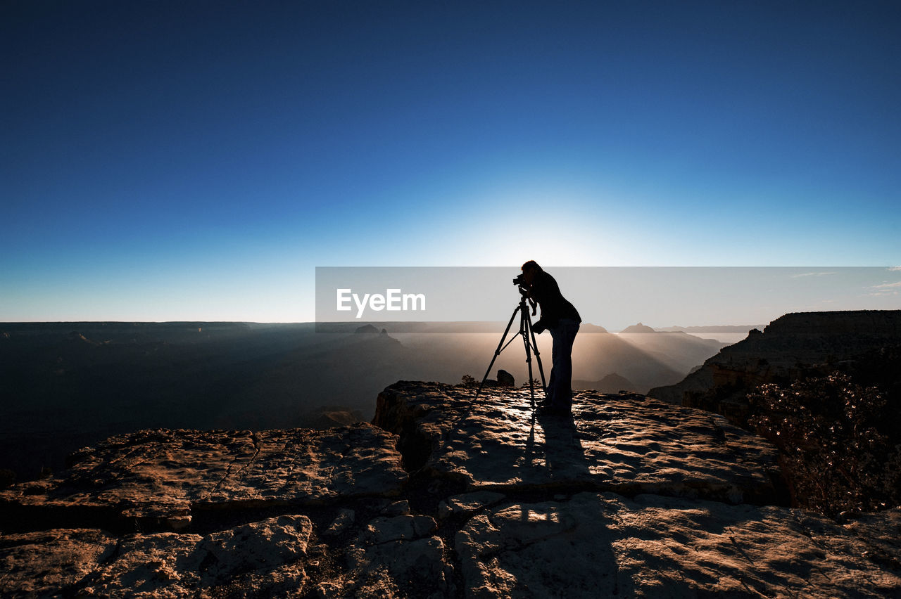 Silhouette Man Photographing Through Camera While Standing On Mountain
