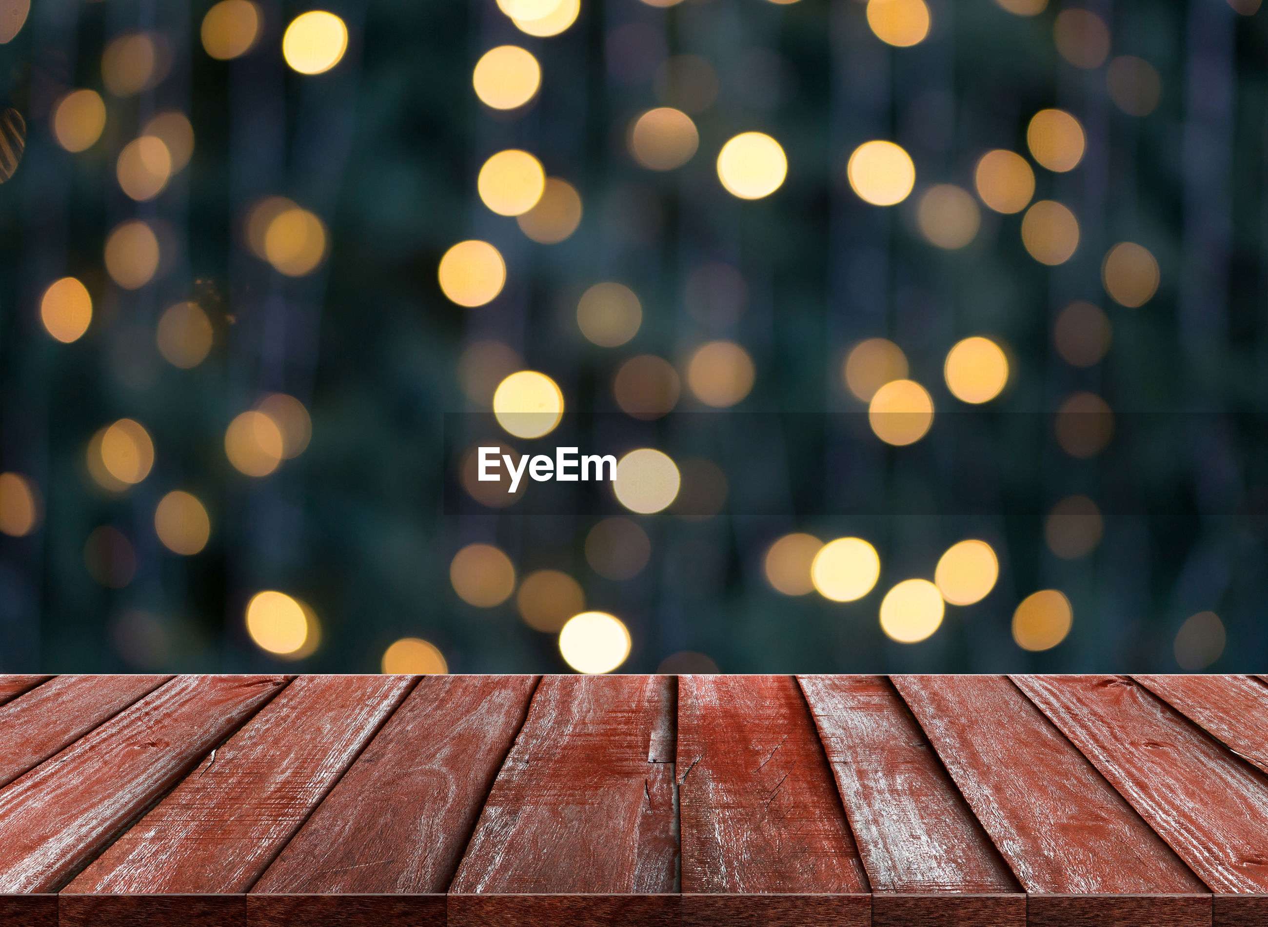 Wooden table against illuminated lights