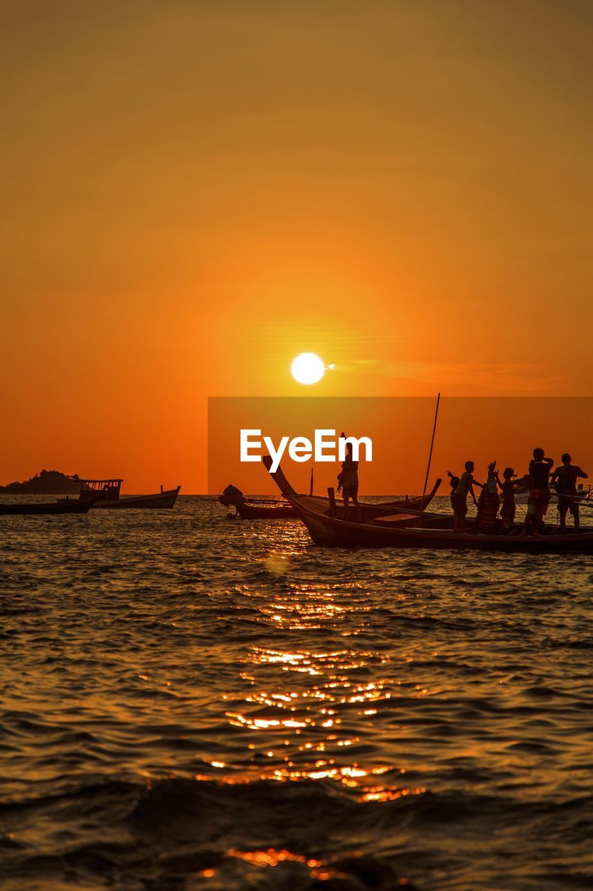 People in boat on sea during sunset