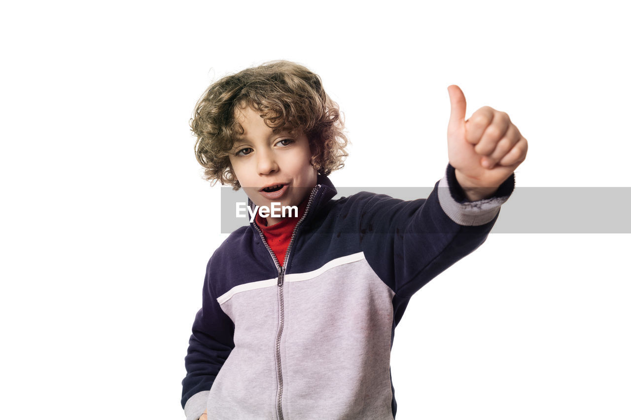 Portrait of boy gesturing while standing against white background