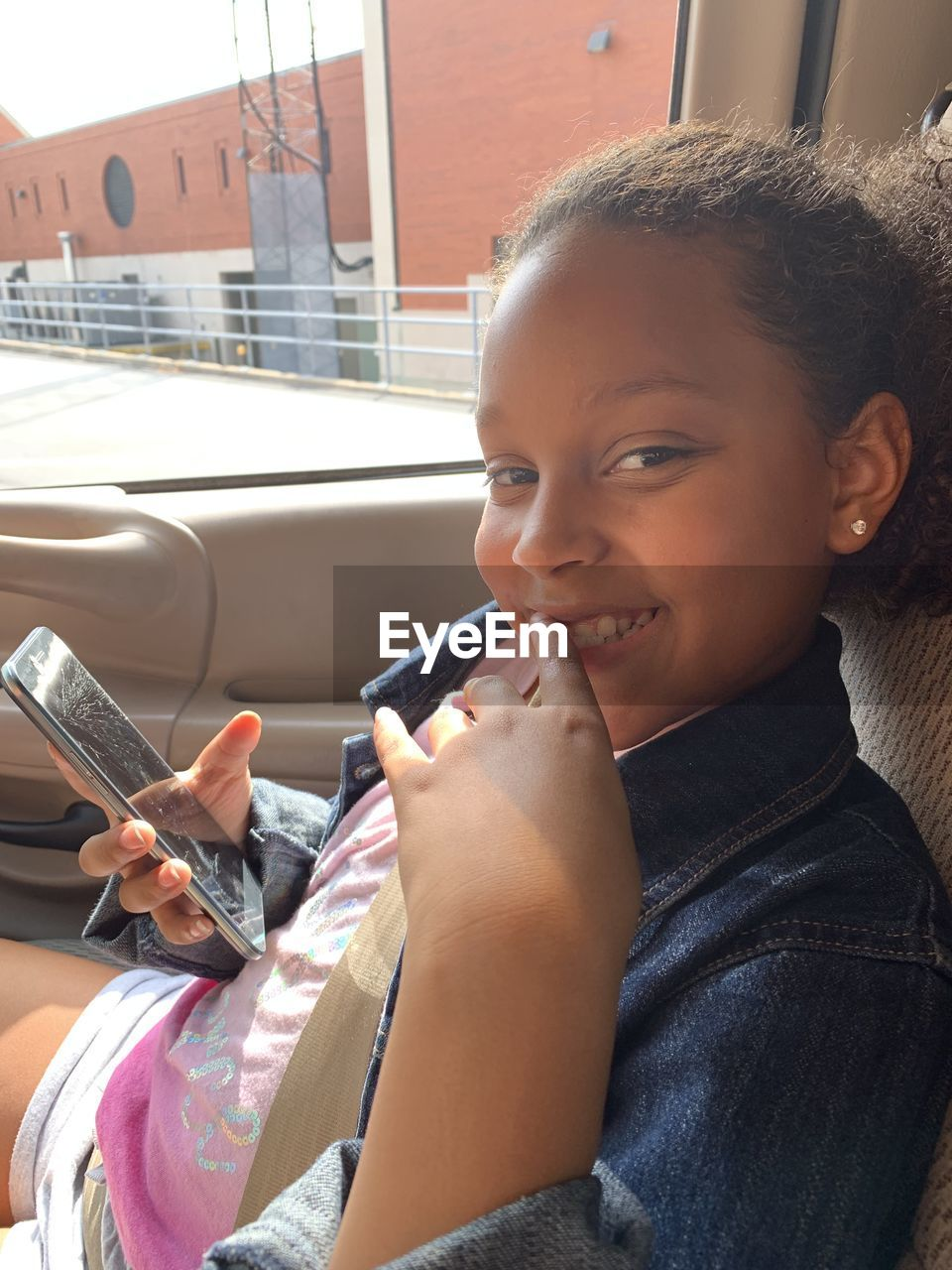 Portrait of smiling girl using mobile phone in car