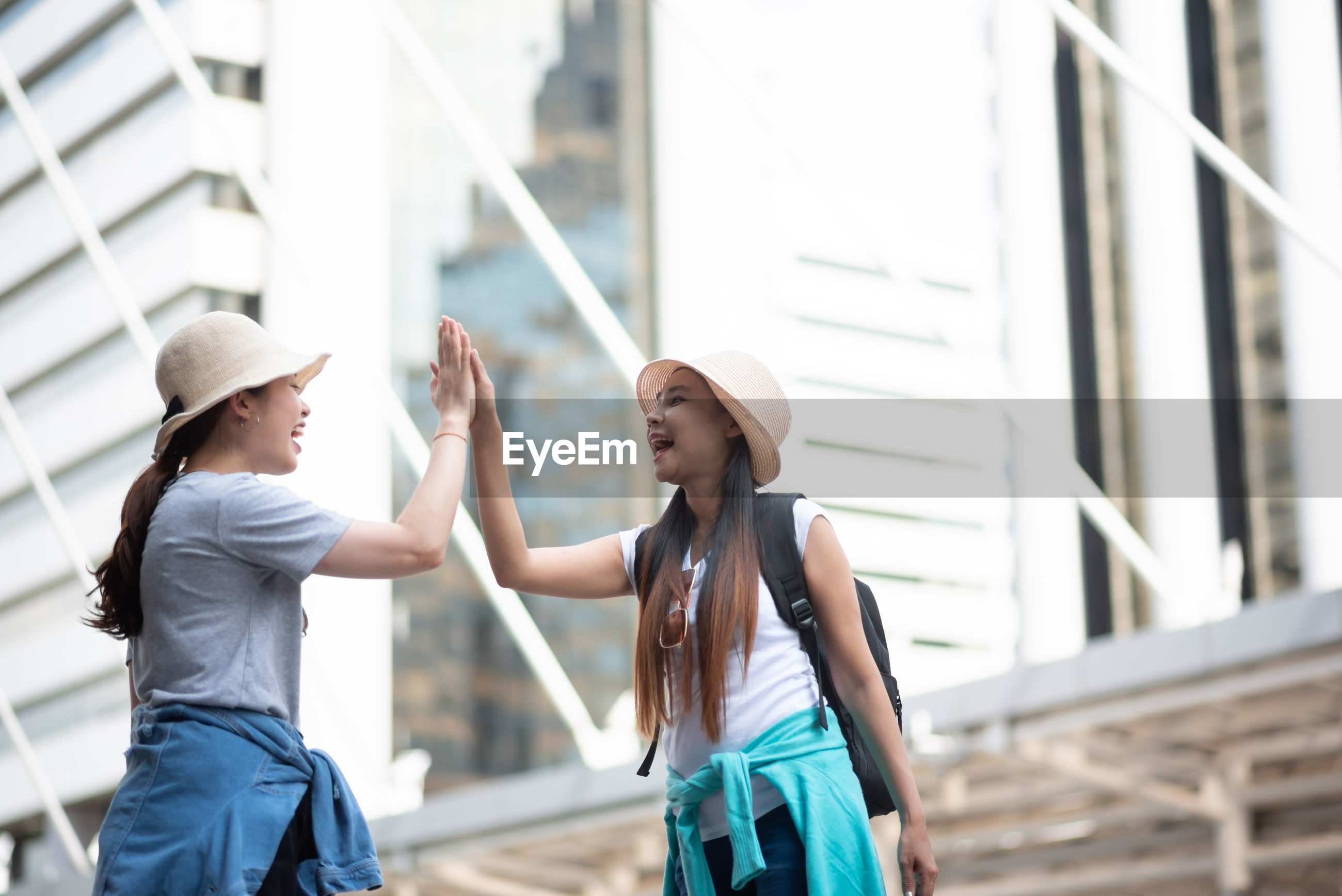 Tourists doing high five while standing in city