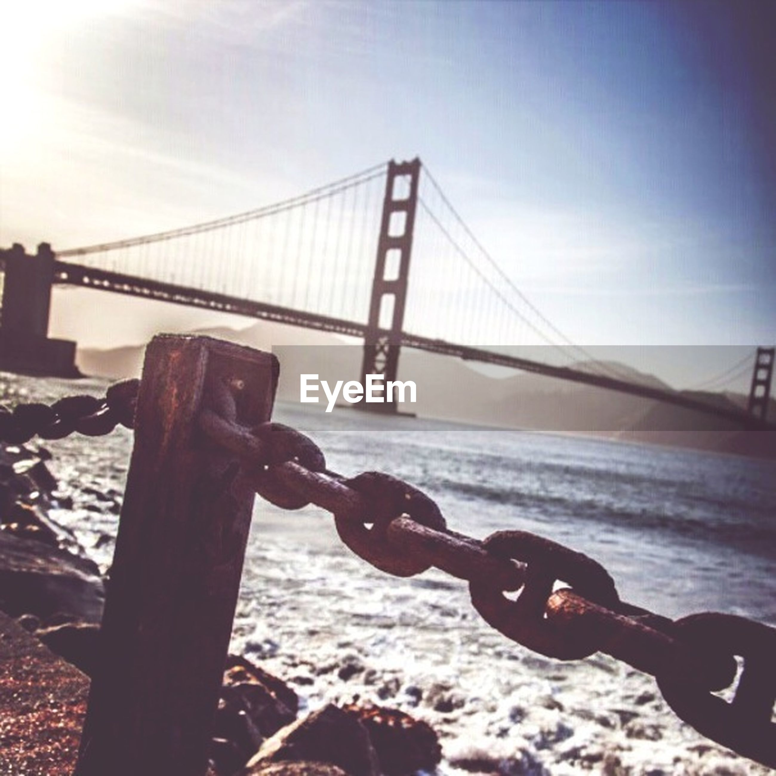 water, metal, sea, sky, bridge - man made structure, connection, railing, metallic, built structure, chain, sunlight, silhouette, protection, beach, strength, outdoors, nature, focus on foreground, river, engineering