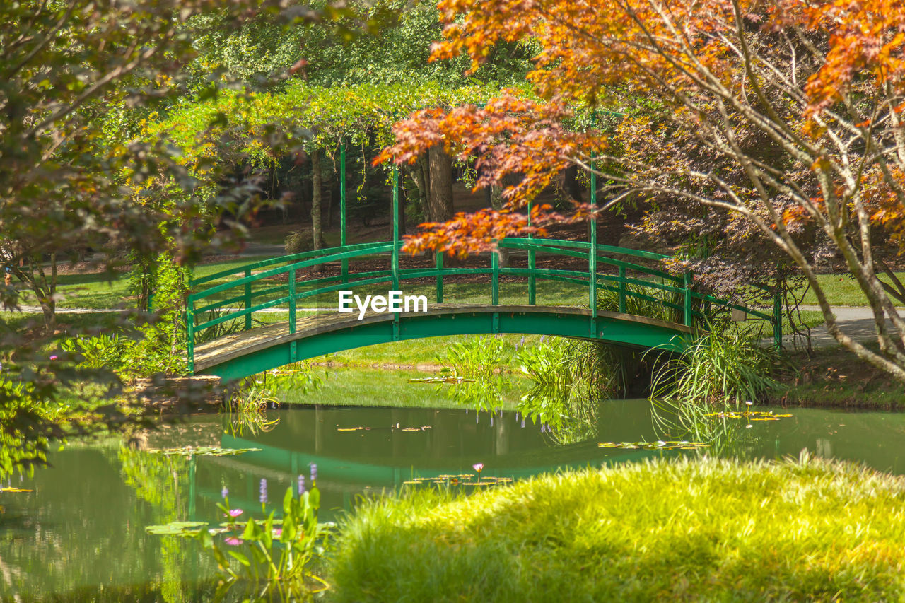 Green footbridge over canal against trees in park