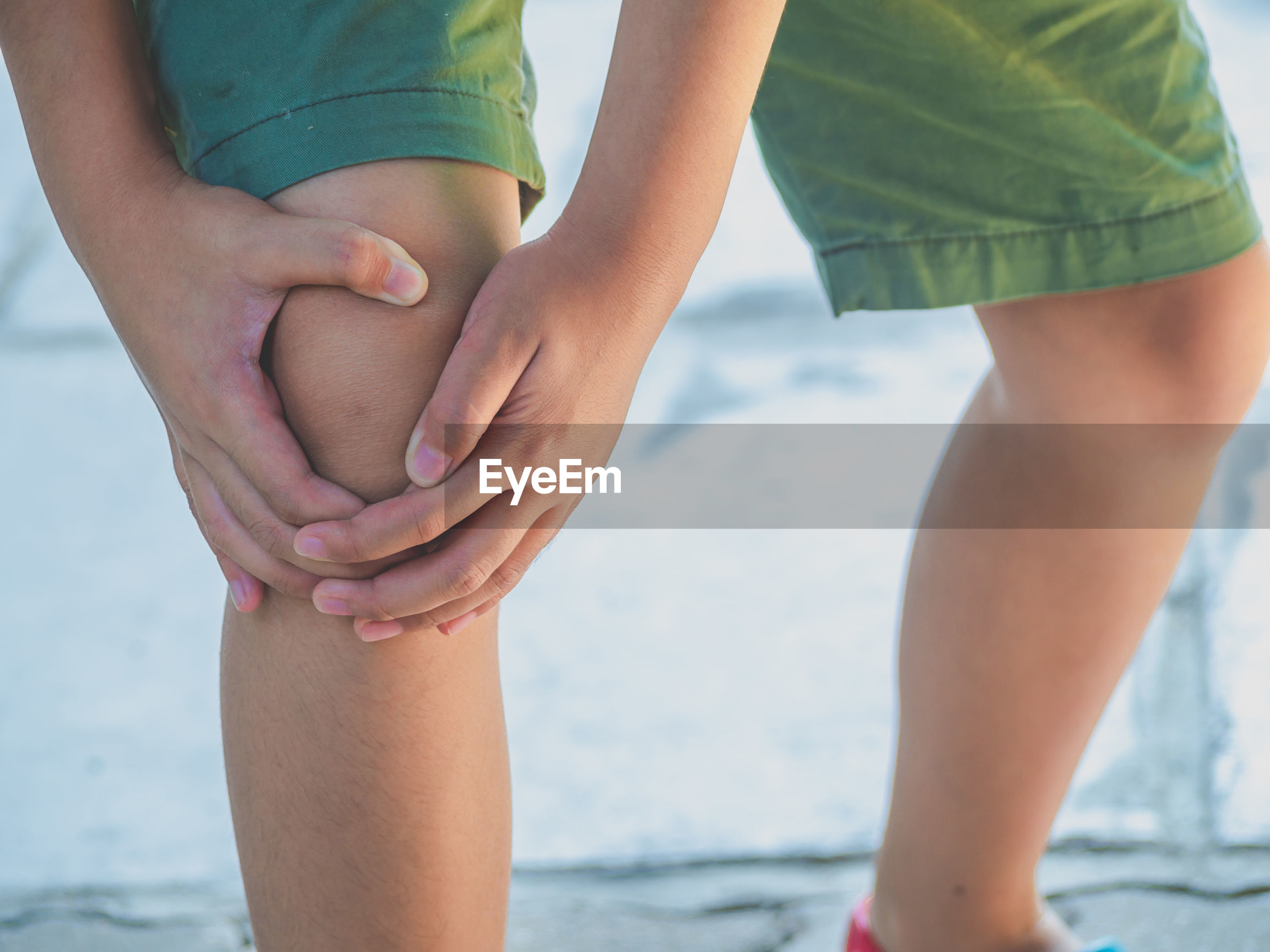 Midsection of boy holding knee
