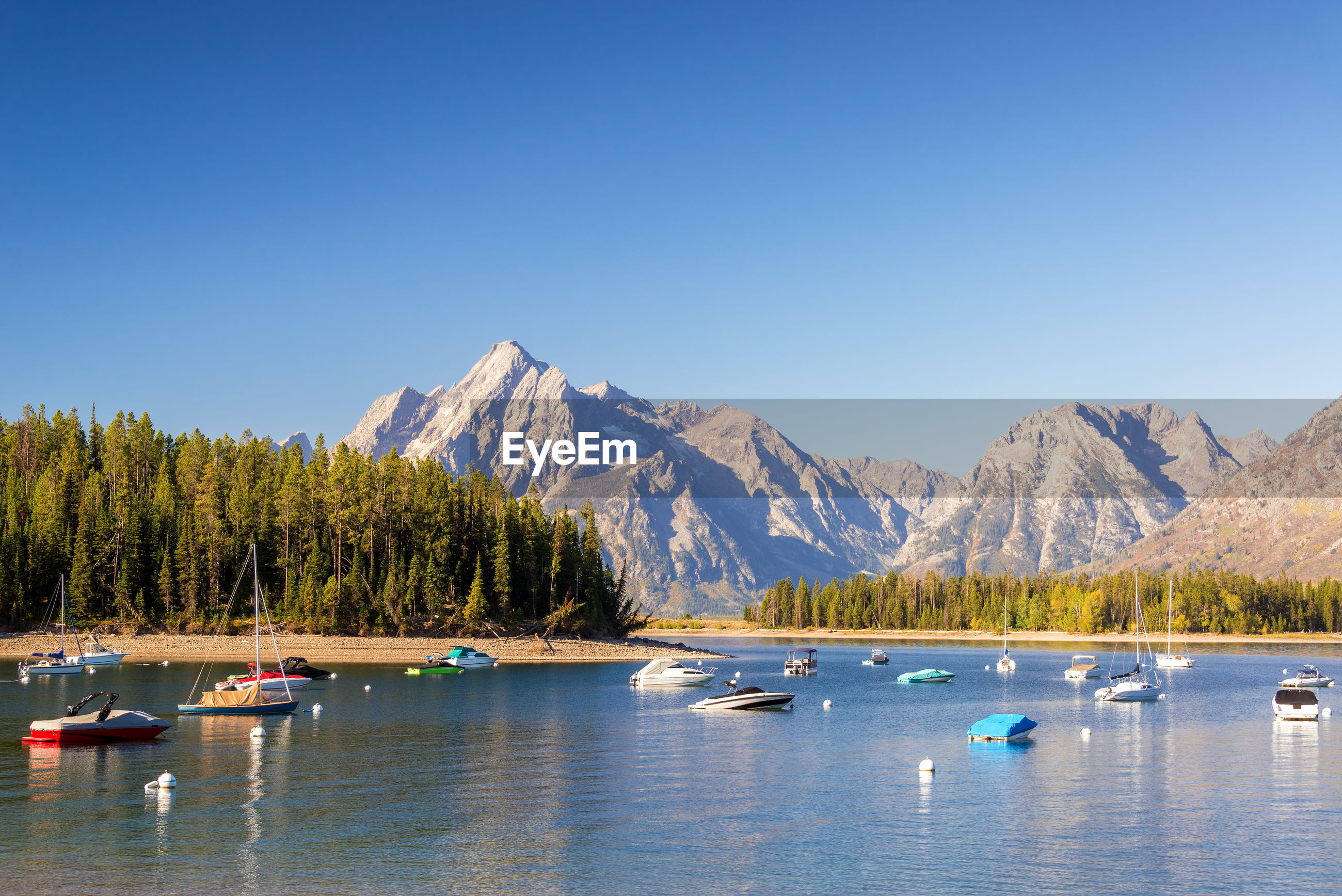 Boats in colter bay with teton mountain range in background in ground teton national park