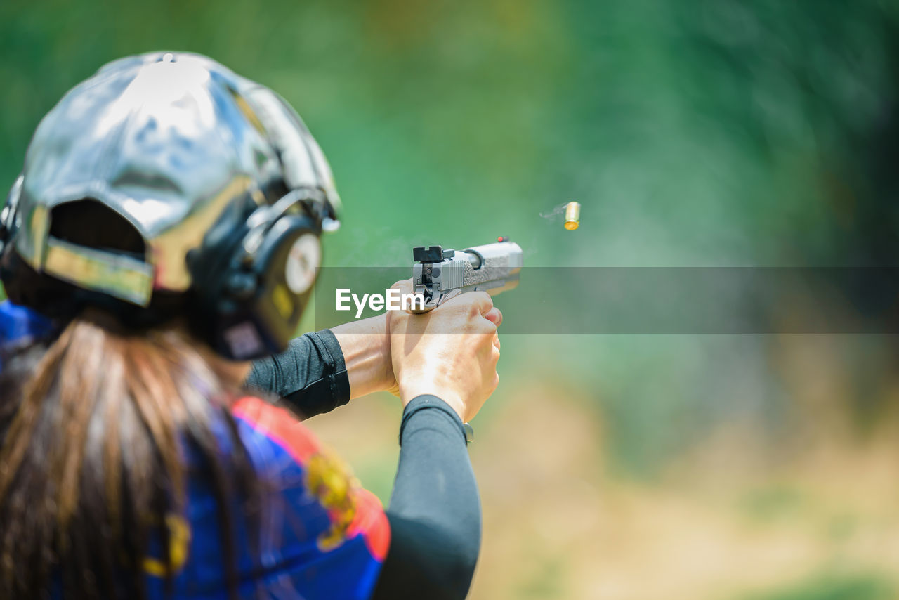 Rear View Of Woman Target Shooting