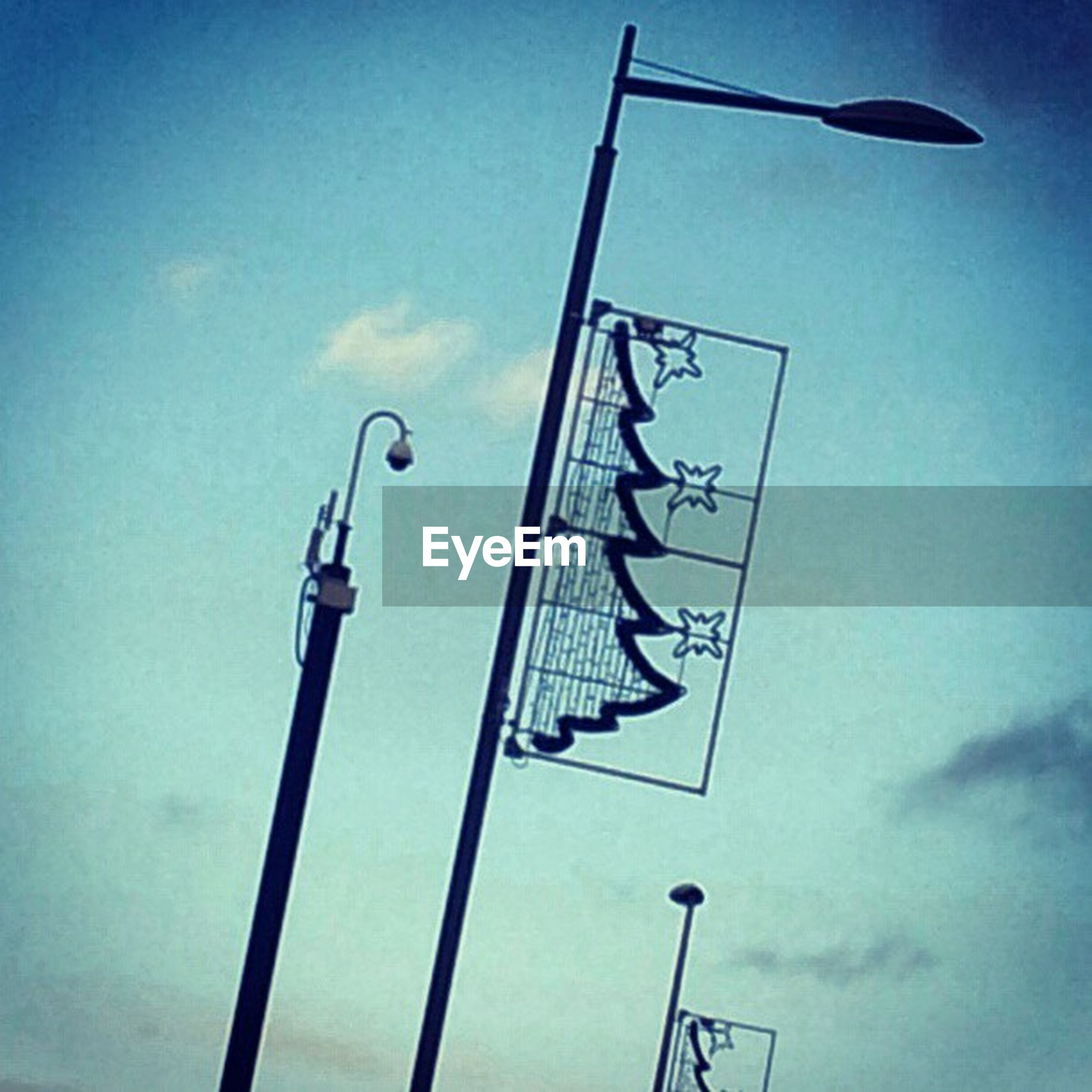 low angle view, sky, blue, street light, pole, lighting equipment, cloud - sky, cloud, no people, day, flag, outdoors, clear sky, hanging, metal, floodlight, sunlight, in a row, identity, communication