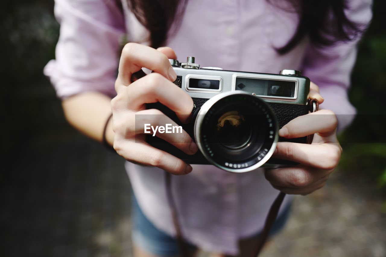 camera - photographic equipment, one person, midsection, photography themes, technology, holding, real people, photographic equipment, photographing, activity, focus on foreground, leisure activity, lifestyles, human hand, front view, women, camera, occupation, hand, photographer, modern, digital camera, outdoors, slr camera, digital single-lens reflex camera, obscured face
